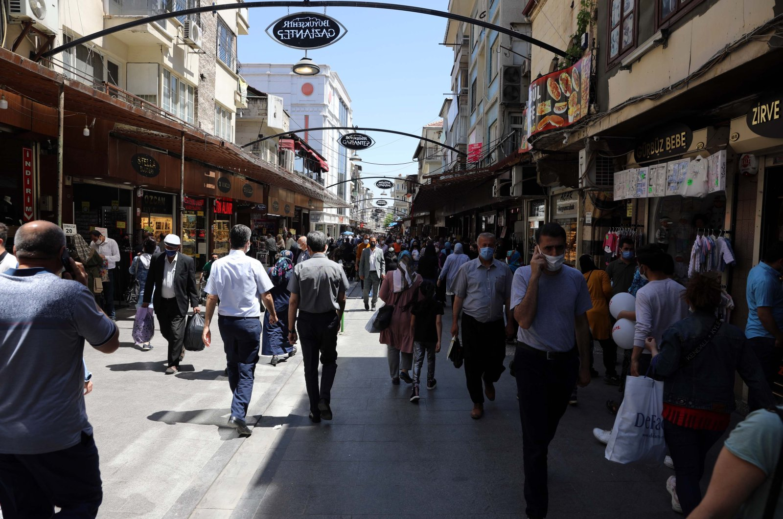People wearing protective masks against COVID-19 walk on a street in Gaziantep, southern Turkey, April 27, 2021. (DHA PHOTO)