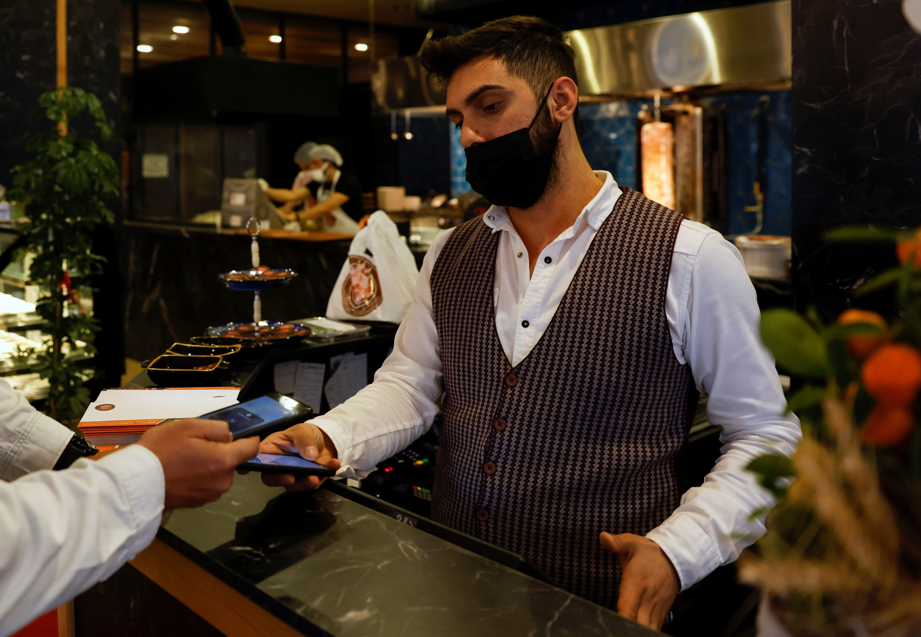 A cashier takes payment via cryptocurrency app at a kebab restaurant that accepts Bitcoin and Dexchain in Istanbul, Turkey, April 27, 2021. (Reuters Photo)