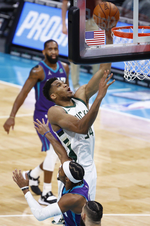Milwaukee Bucks Giannis Antetokounmpo dunks the ball against Charlotte Hornets' Devonte' Graham during an NBA game at Spectrum Center, Charlotte, North Carolina, U.S., April 27, 2021. (AFP Photo)