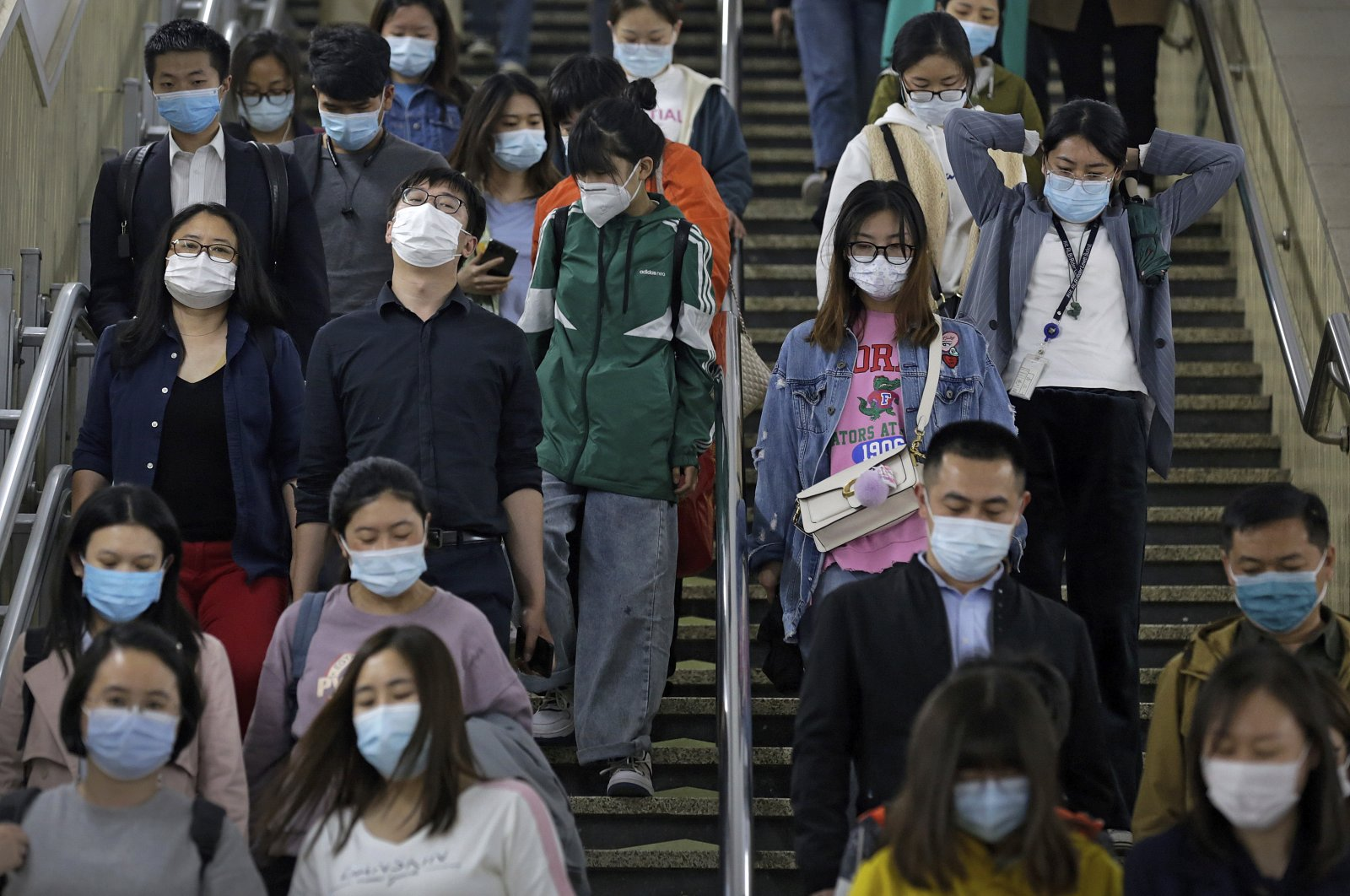 People wearing face masks to help curb the spread of the coronavirus walk down the staircase leading to a subway station during the evening rush hour in Beijing, China, April 26, 2021. (AP Photo)