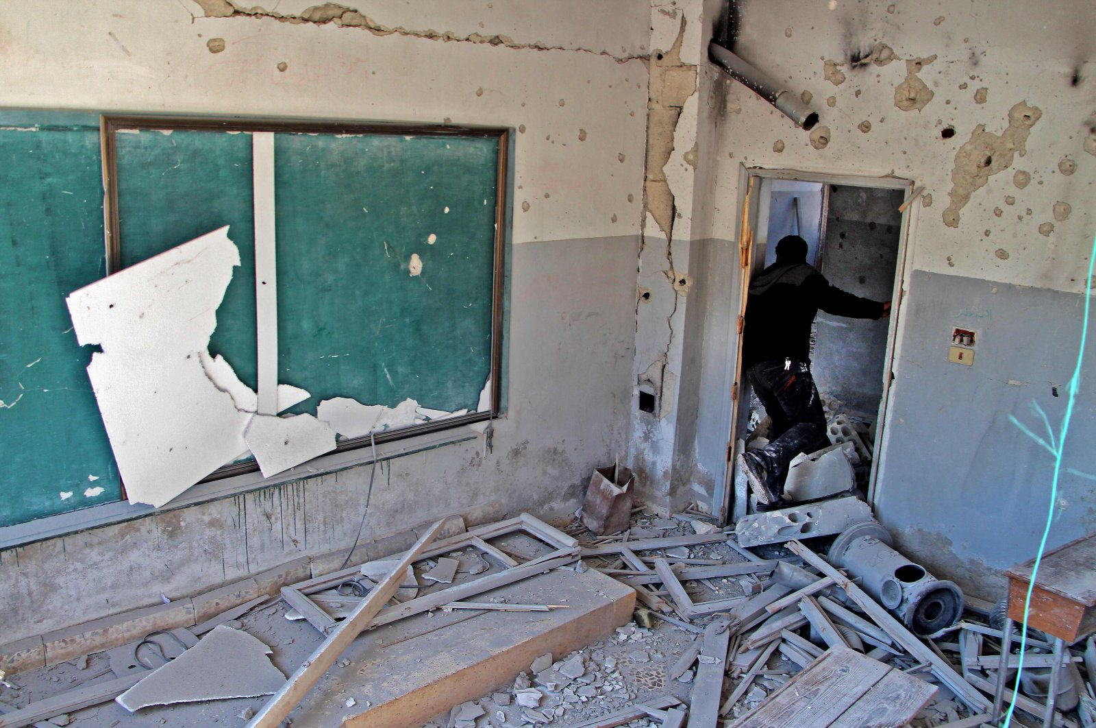 A displaced Syrian man checks a school that was reportedly targeted by Bashar Assad regime's airstrike near the town of Adwan, Idlib province, northwestern Syria, March 3, 2020. (AFP Photo)