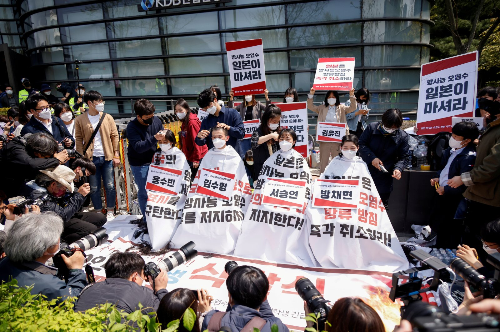 South Korea university students get their heads shaved during a protest against Japan's decision to release contaminated water from its crippled Fukushima nuclear plant into the sea, in front of the Japanese embassy, in Seoul, South Korea, April 20, 2021.  (REUTERS Photo)