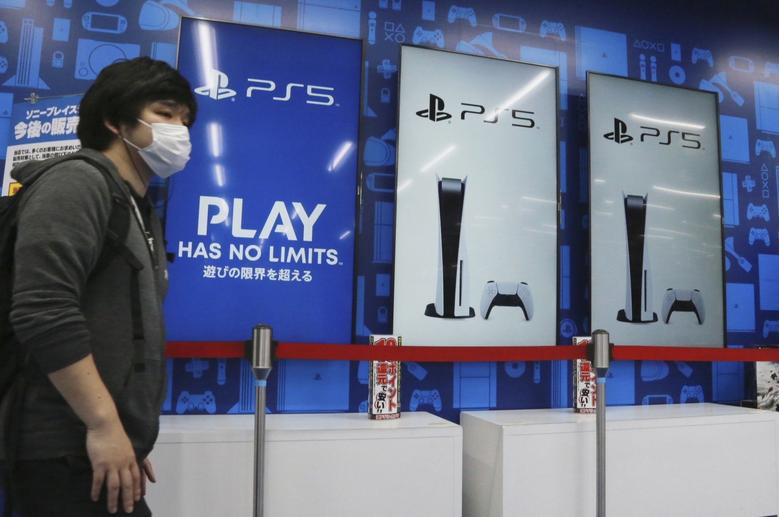 A man stands near promotional pictures of the Play Station 5 at an electronics retail chain store in Tokyo, Japan, April 28, 2021. (AP Photo)