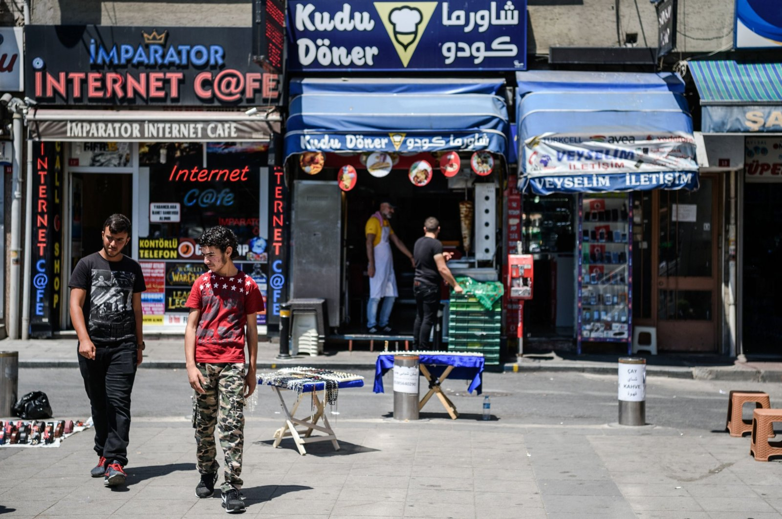 Syrian men walk pass a Syrian fast food restaurant in the Fatih district of Istanbul, Turkey, July 4, 2016. (AFP Photo)