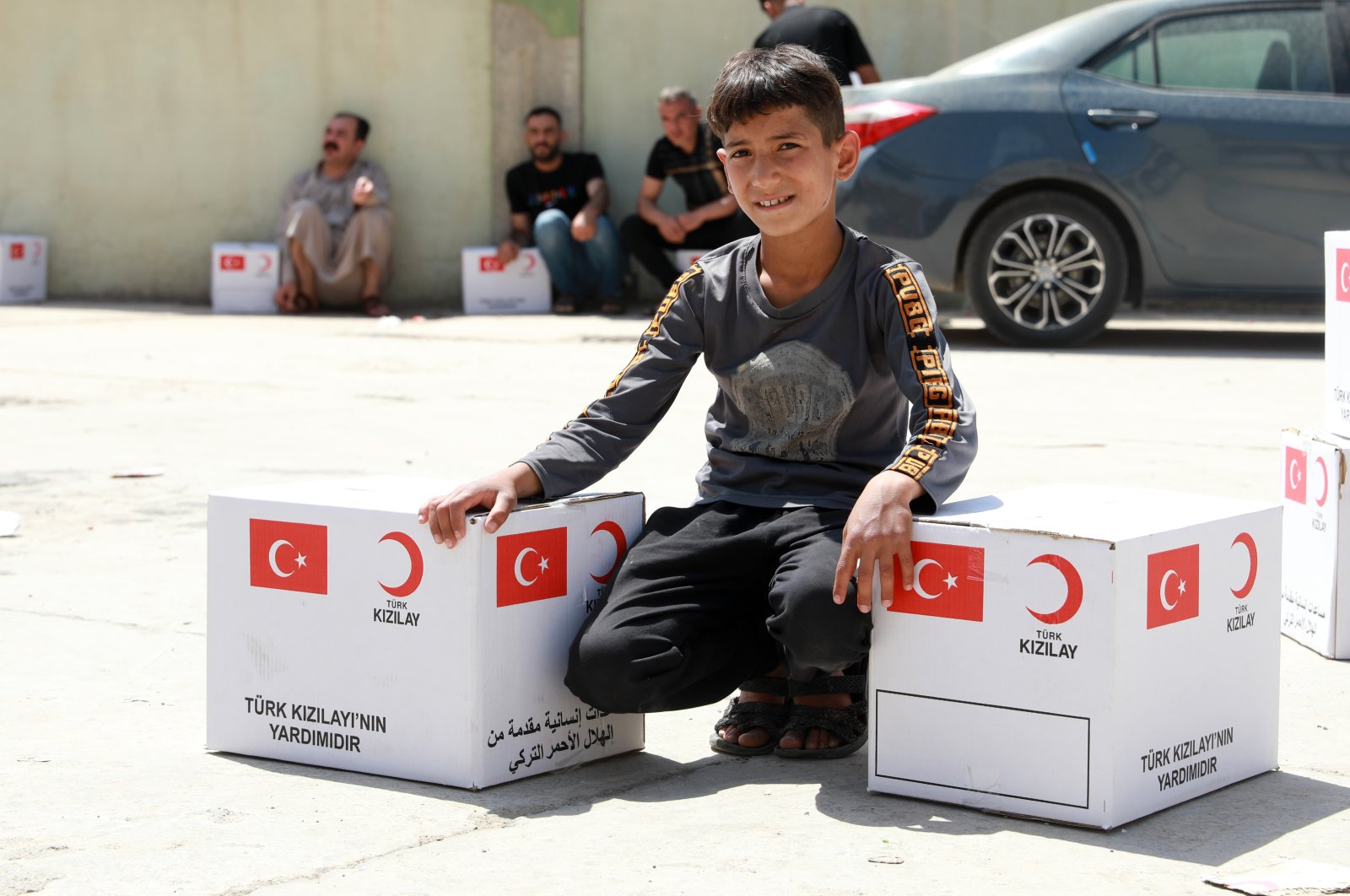 An orphan receives aid packages provided by the Turkish Red Crescent, Mosul, Iraq, April 28, 2021. (AA Photo)