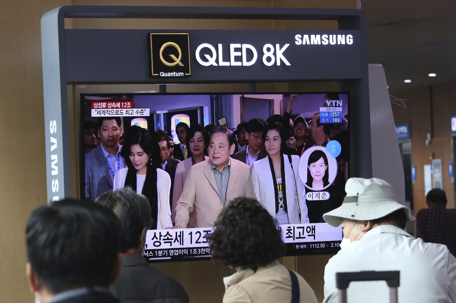 People watch a TV screen showing a file image of the late Samsung Electronics chairperson Lee Kun-Hee (C) and his daughters during a news program at Seoul Railway Station in Seoul, South Korea, April 28, 2021. (AP Photo)