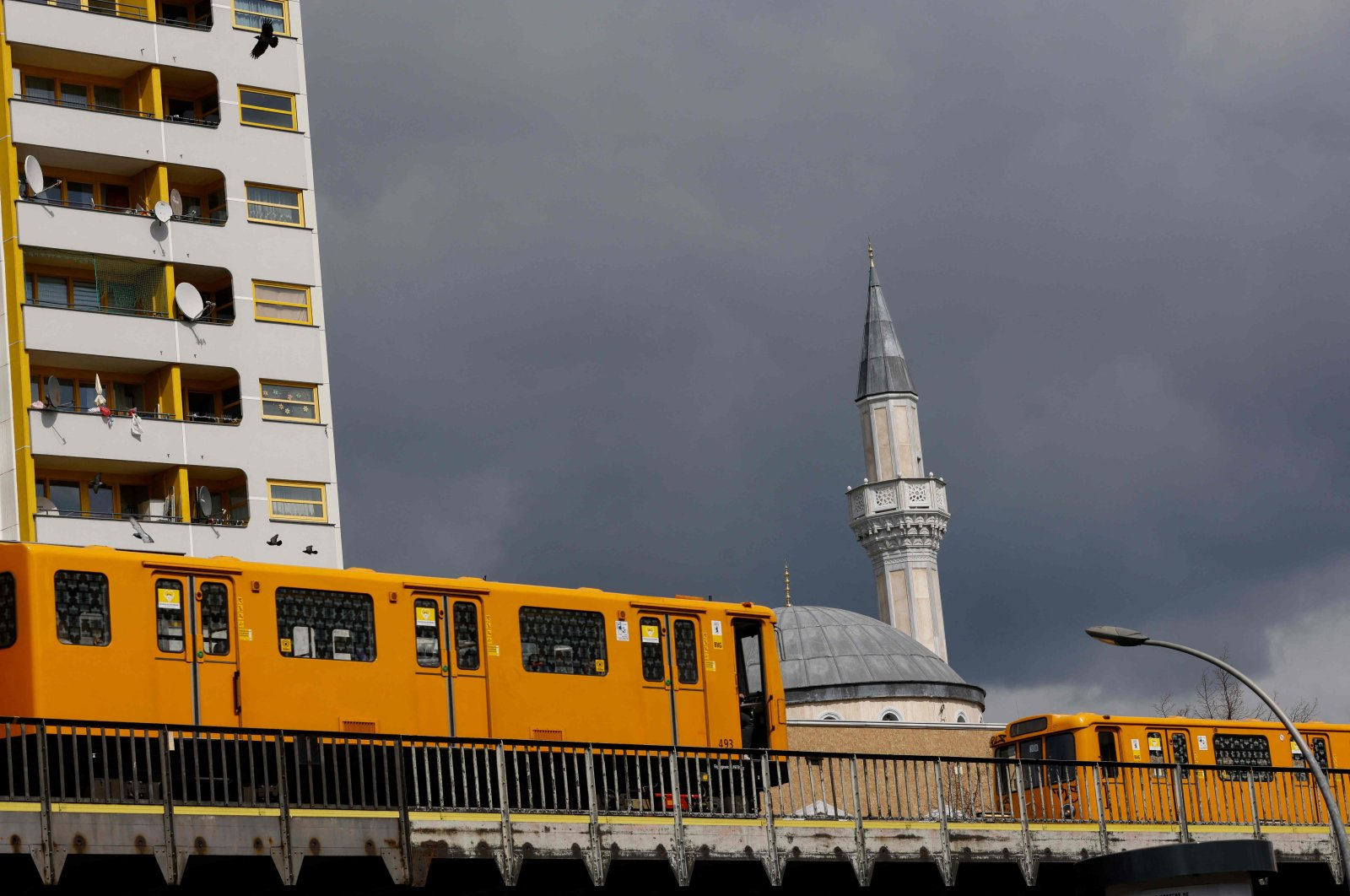 Two U-bahn subway trains drive past the Mevlana Mosque in Berlin's Kreuzberg district on April 14, 2021, a day after the start the Muslim holy fasting month of Ramadan. (Photo by David GANNON / AFP)