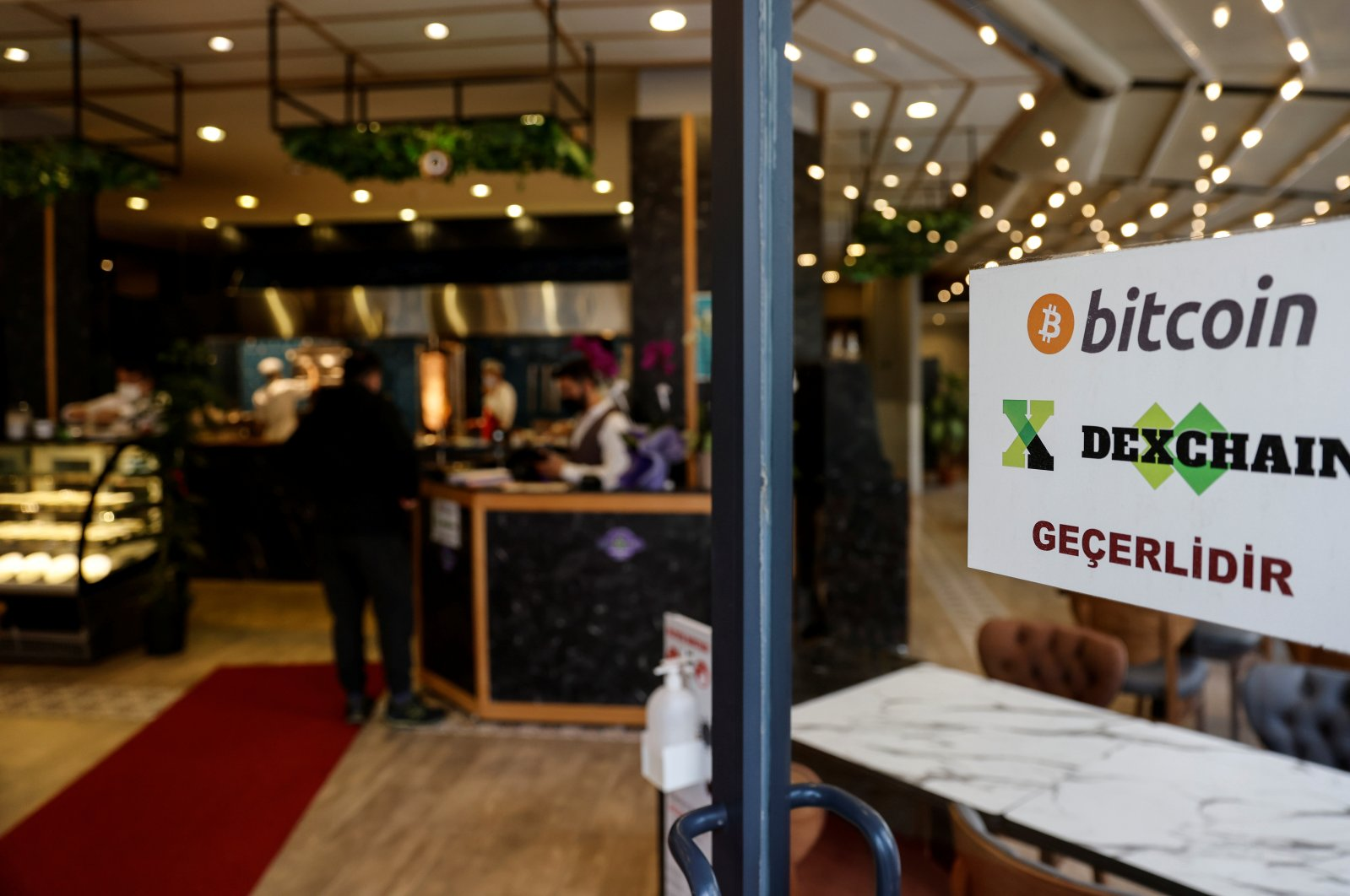 """A sign at the entrance door of a kebab restaurant reads """"We accept Bitcoin, Dexchain"""" in Istanbul, Turkey, April 27, 2021. (Reuters Photo)"""