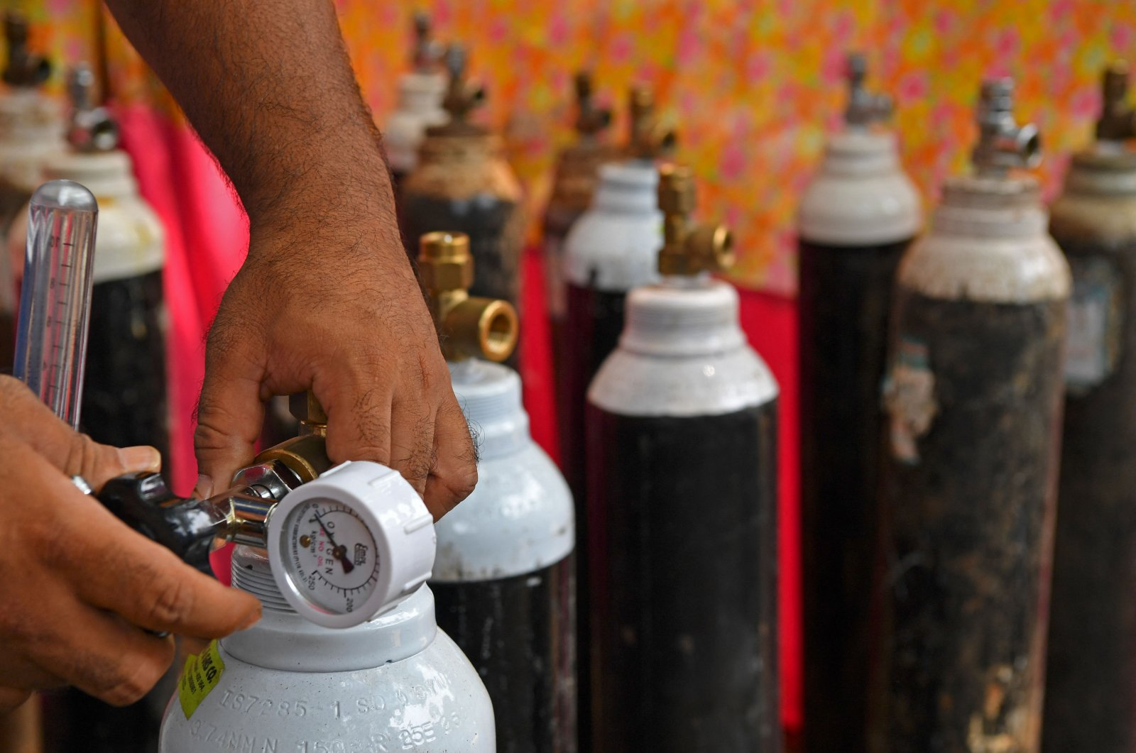 Local resident Shahnawaz Shaikh, who sold his SUV to raise funds in order to start a free service to provide oxygen cylinders to the needy amid the coronavirus pandemic, checks the pressure of an oxygen cylinder at a distribution center in a slum in Mumbai, India, April 28, 2021. (AFP Photo)