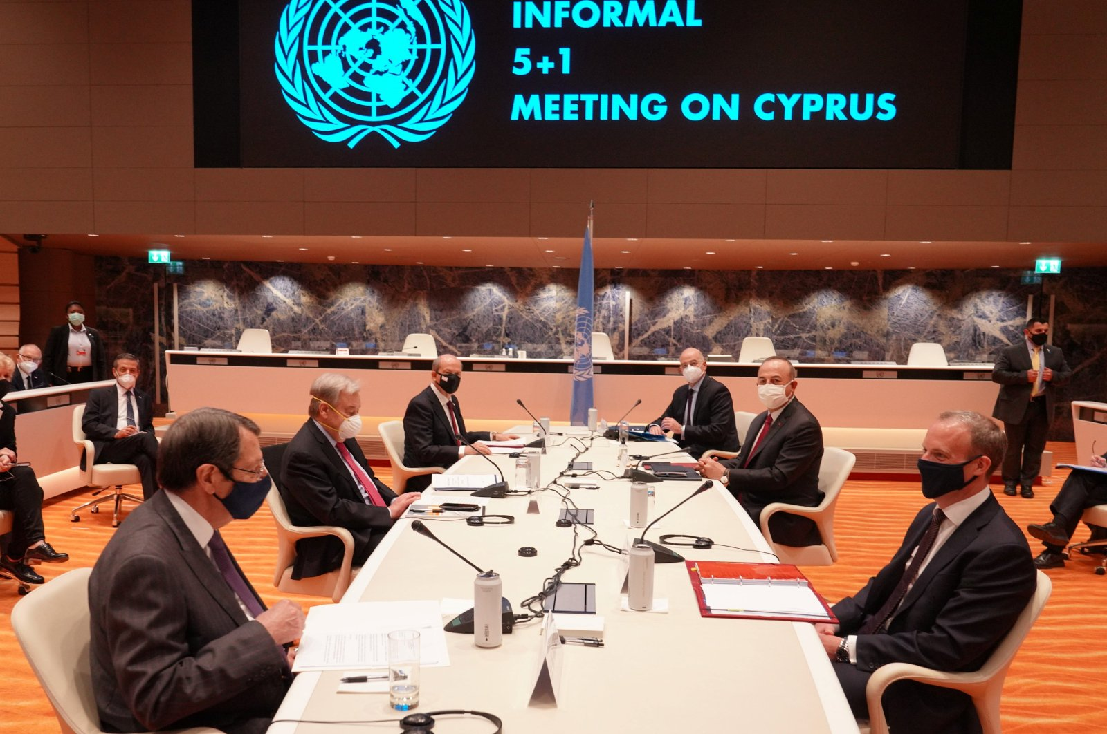 (L side, L to R) United Nations Secretary-General Antonio Guterres, Greek Cypriot leader Nicos Anastasiades and Turkish Cypriot President Ersin Tatar. (R side, L to R) Greek Foreign Minister Nikos Dendias, Turkish Foreign Minister Mevlüt Çavuşoğlu and British Foreign Secretary Dominic Raab talk during a meeting at the United Nations European headquarters in Geneva, Switzerland April 28, 2021. (PIO/Handout via Reuters)