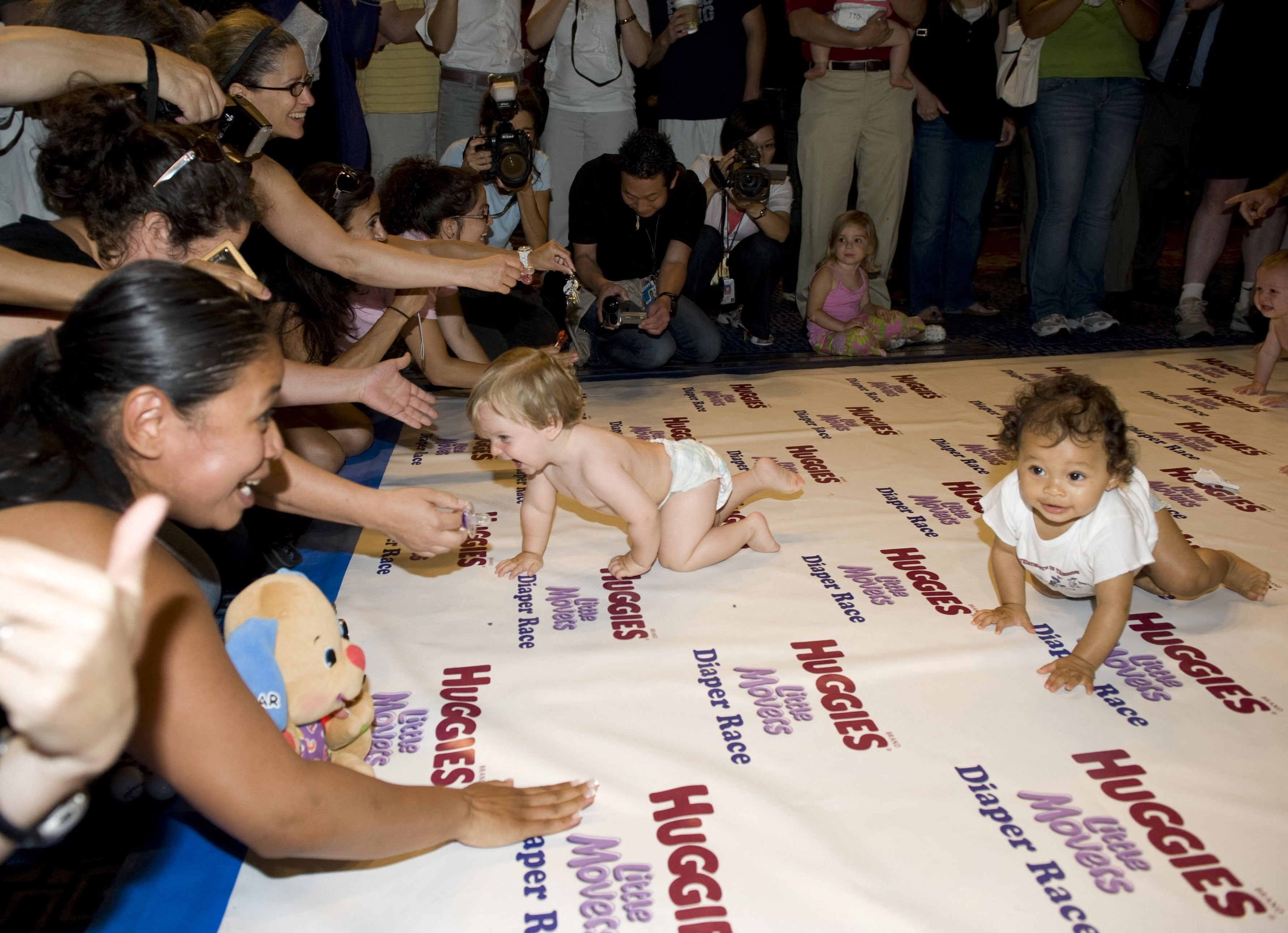 Babies are coached toward the finish line by their parents during a baby race in New York City, New York, the U.S., July 24, 2009. (AFP Photo)