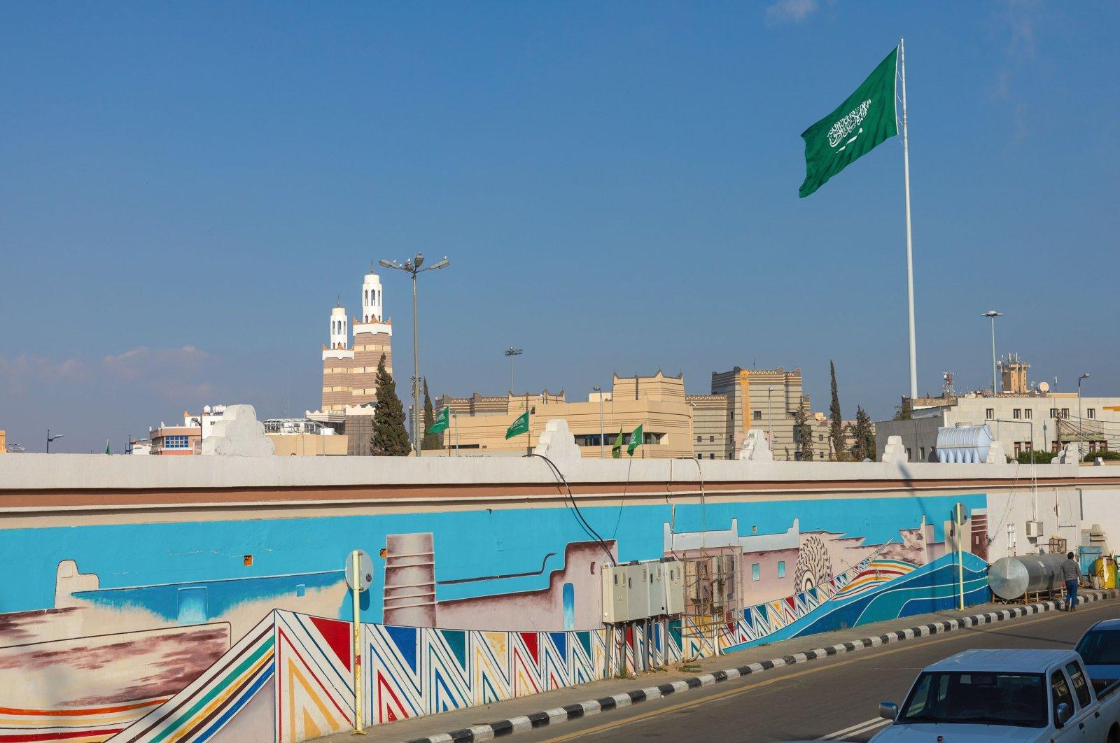 The Saudi Arabian flag flies in front of a fresco, Asir province, Abha, Saudi Arabia, Jan 3, 2020. (Getty Images)