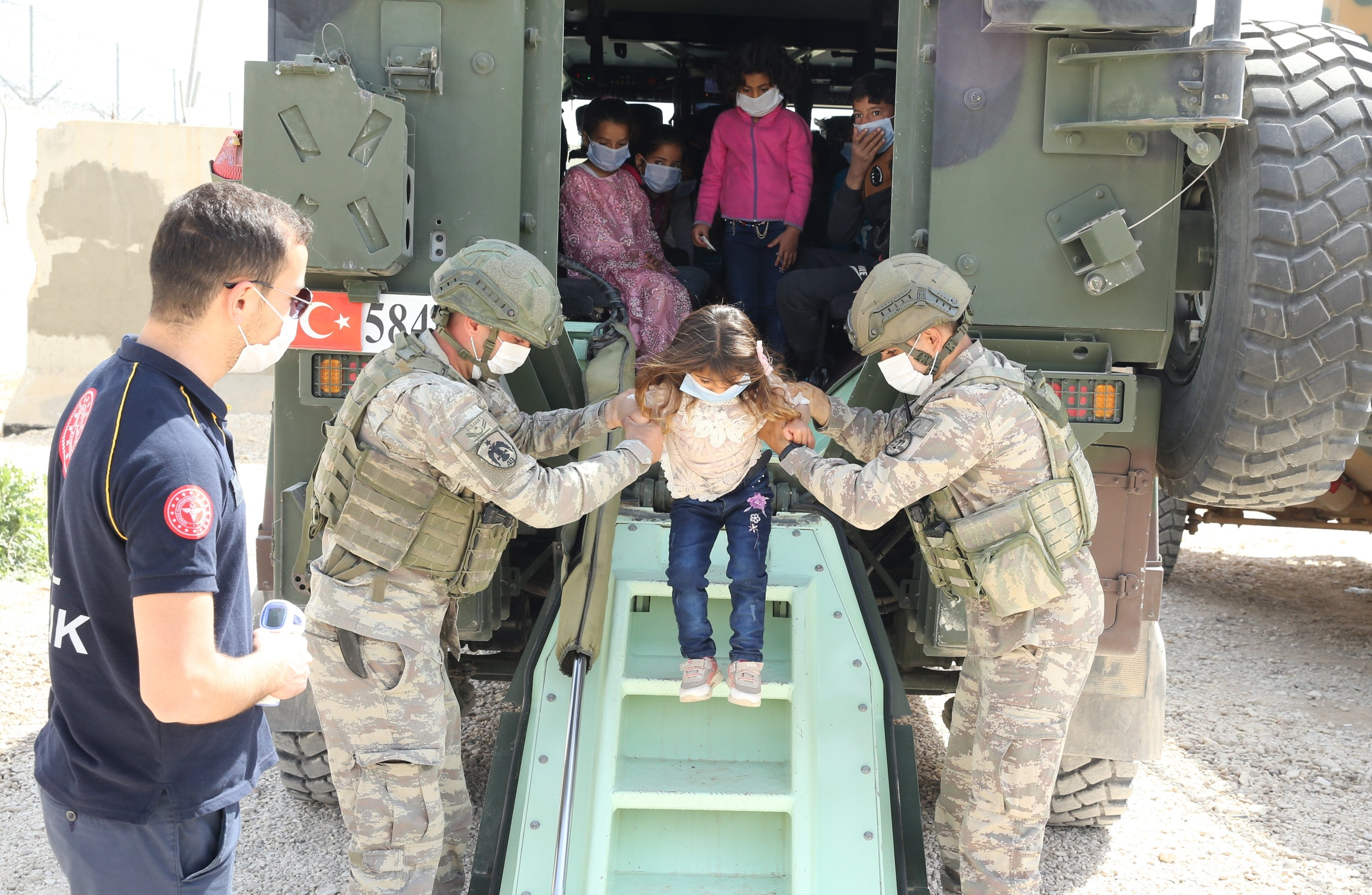 Turkish soldiers help a Syrian child to get off an armored vehicle for a daulong trip in Mardin, Turkey, April 28, 2021. (AA)