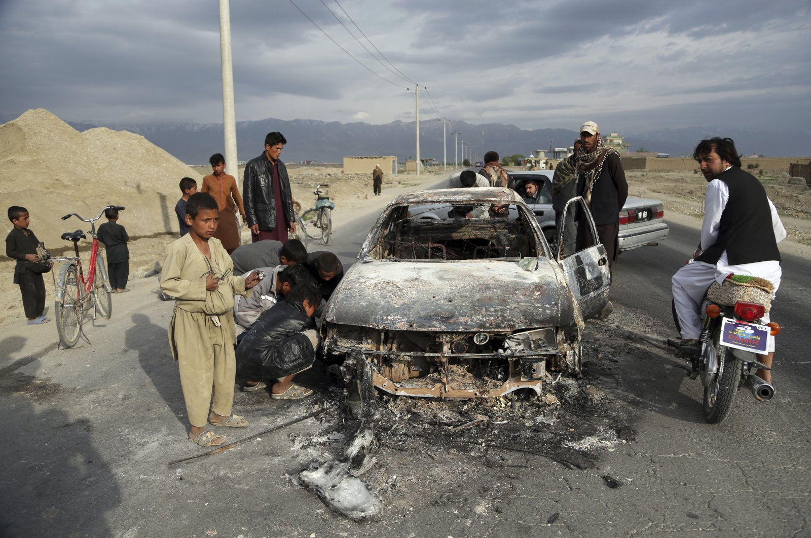Afghans look at a civilian vehicle burnt after being shot by U.S. forces after an attack near the Bagram Air Base, north of Kabul, Afghanistan, April 9, 2019. (AP Photo)