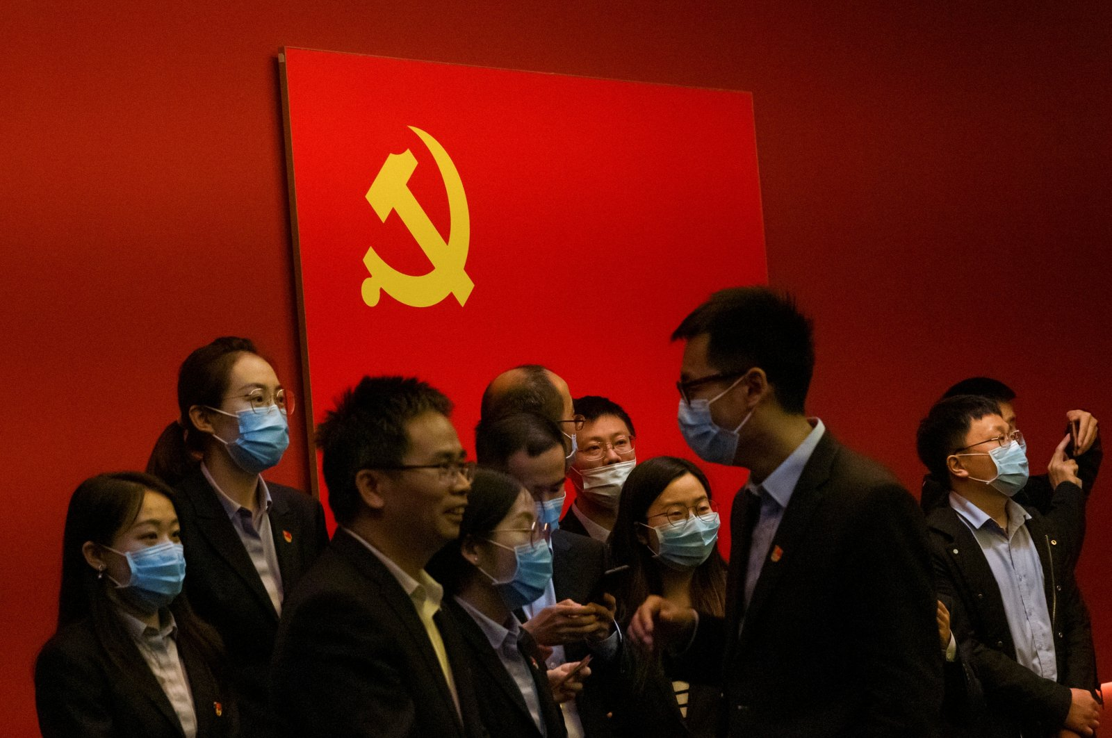 People stand in front of the Chinese national flag at an exhibition marking the 100th founding anniversary of the Chinese Communist Party (CCP) in Beijing, China, April 22, 2021.  REUTERS/Thomas Peter