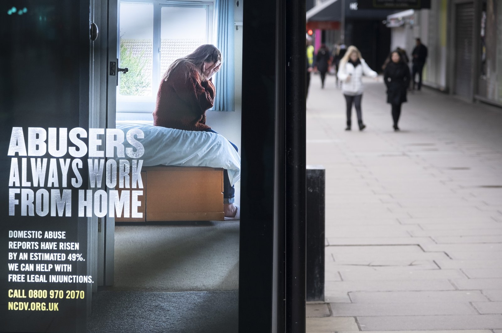 """A bus stop advertisement for the National Centre for Domestic Violencesays """"Abusers always work from home"""" during the national COVID-19 lockdowns in London, the U.K., March 4, 2021. (Getty Images)"""