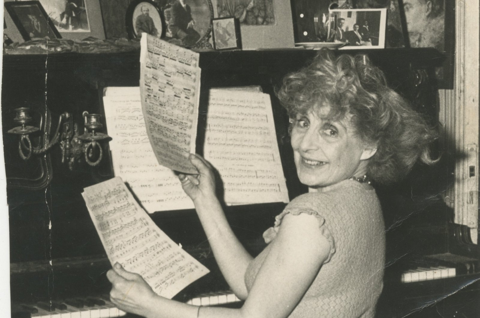 Aliye Berger poses with pages of a music notebook in front of her piano. (Courtesy of SALT Research)
