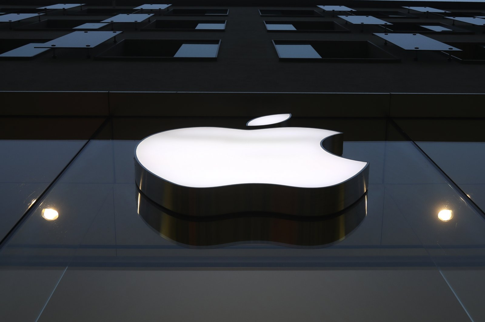 The logo of Apple is illuminated at a store in the city center in Munich, Germany, Dec. 16, 2020. (AP Photo)