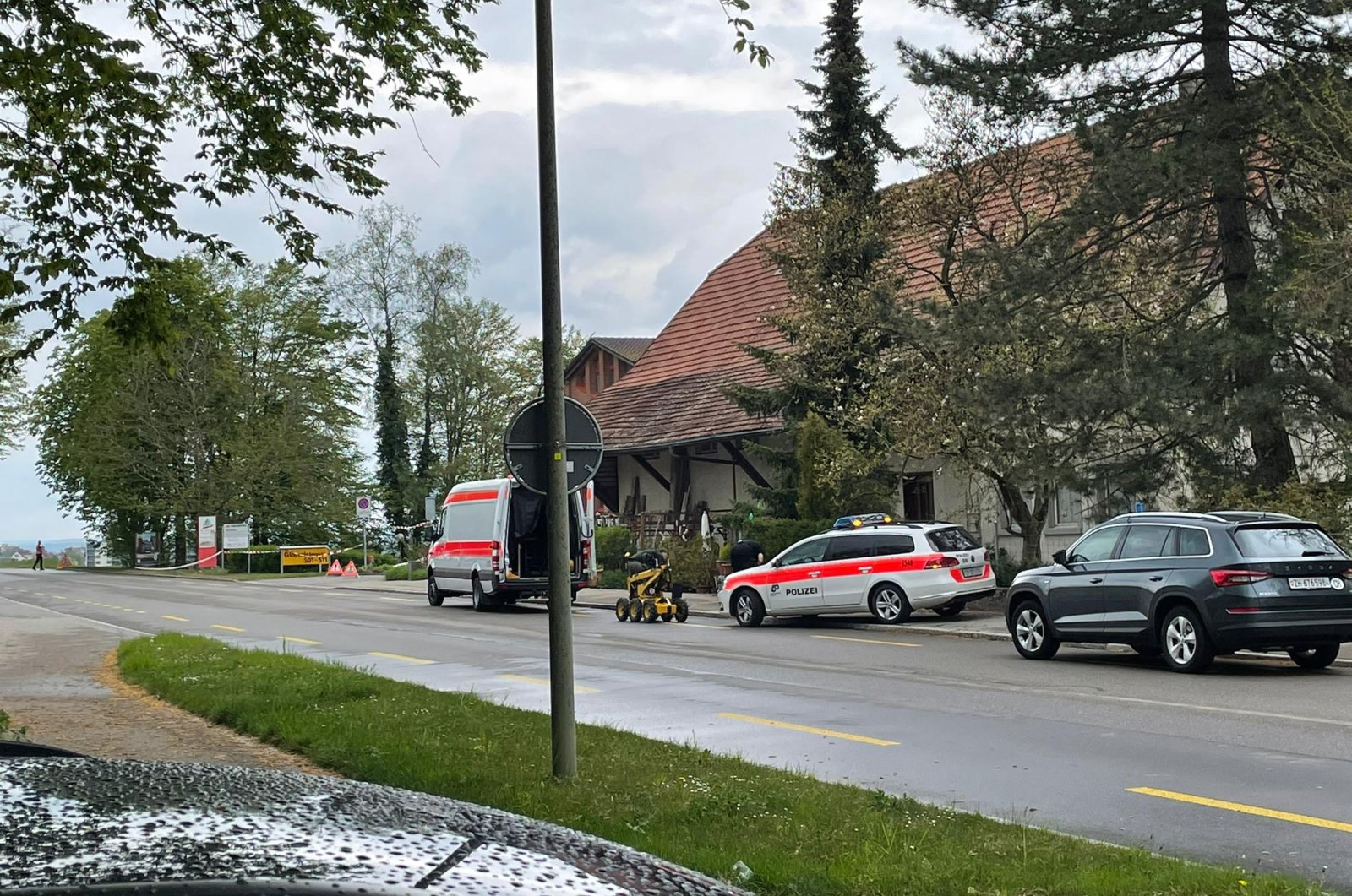 Government vehicles near are parked near where a bomb that was ready to explode was found in the mailbox of the headquarters of the Swiss Turkish Society (ITT), Rumlang, Switzerland, April 30, 2021. (AA)