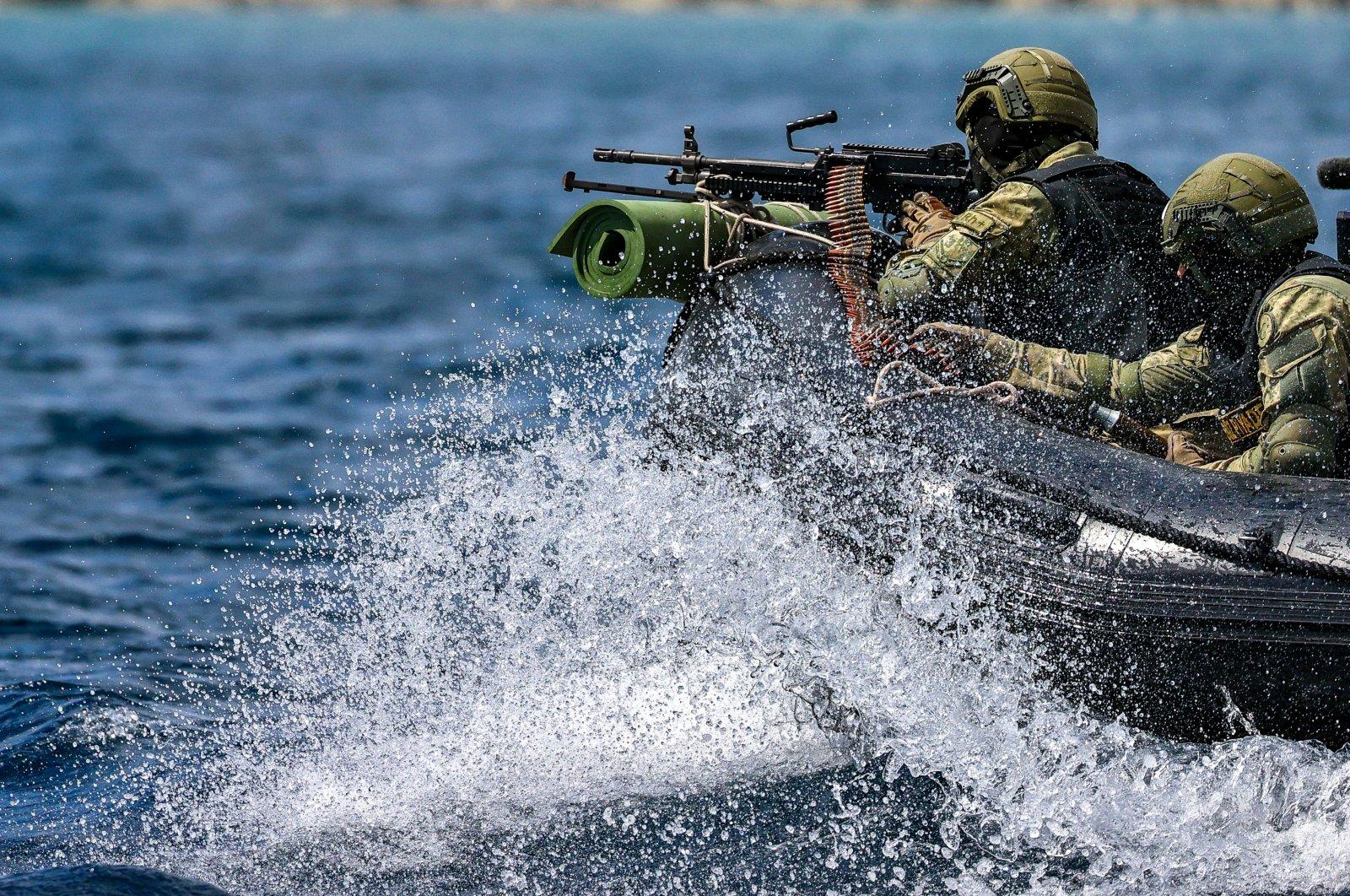 Soldiers approach a vessel aboard a boat, in Izmir, western Turkey, April 29, 2021. (AA PHOTO)