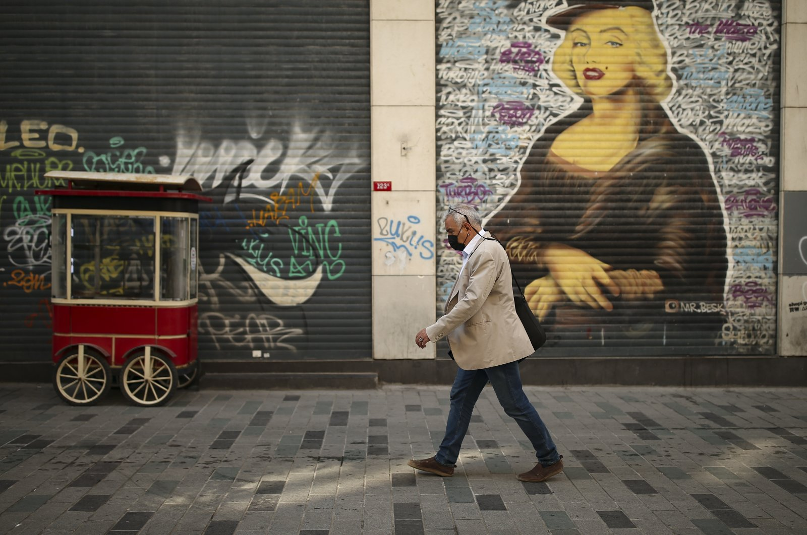 A man walks on a virtually empty Istiklal Street, the main shopping street of Istanbul, with shops closed, April 30, 2021. (AP)