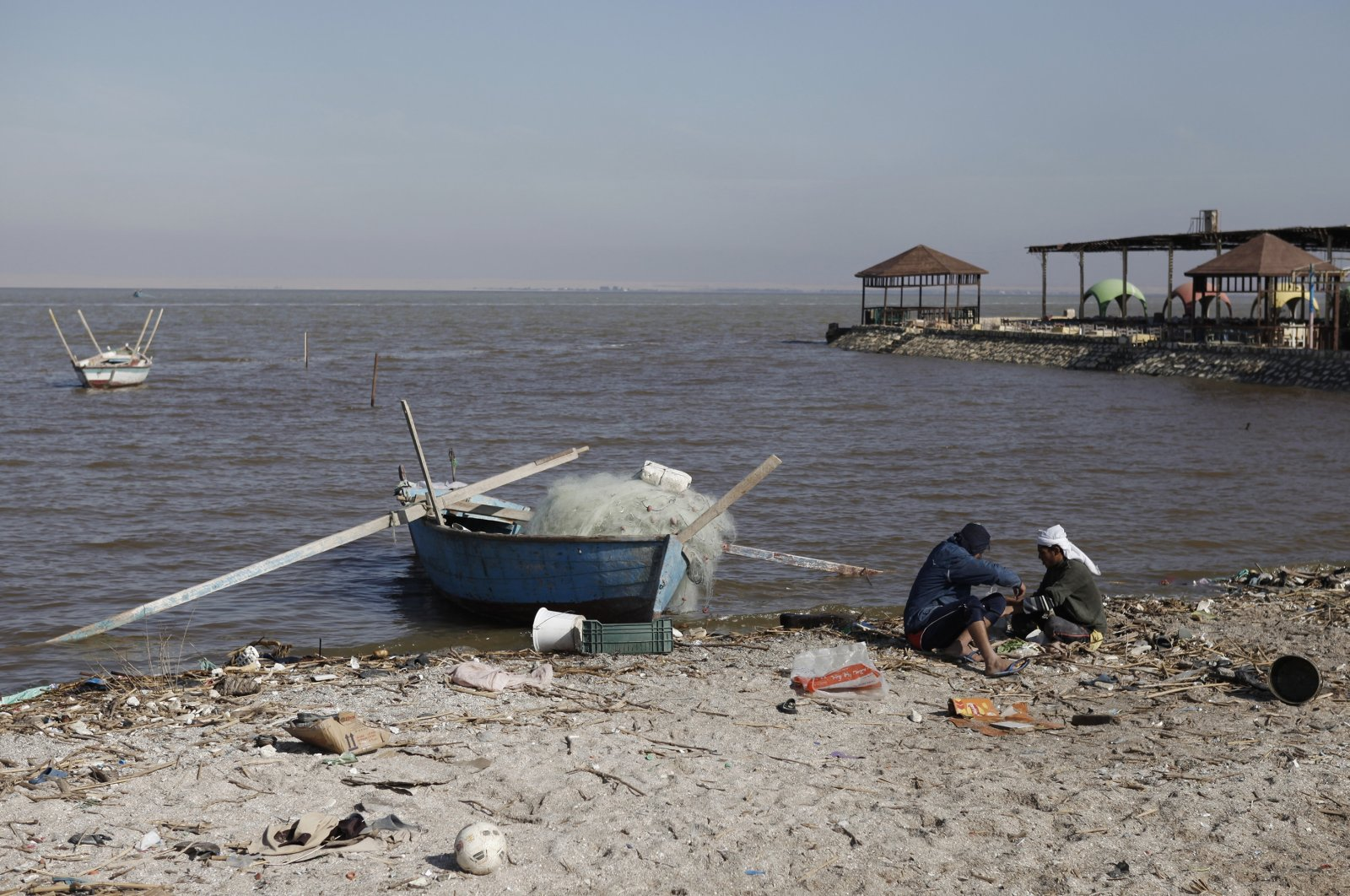 Egyptian fishermen sit by a small fishing boat on Lake Qaroun in Fayoum, Egypt, Jan. 15, 2014. (Getty Images)