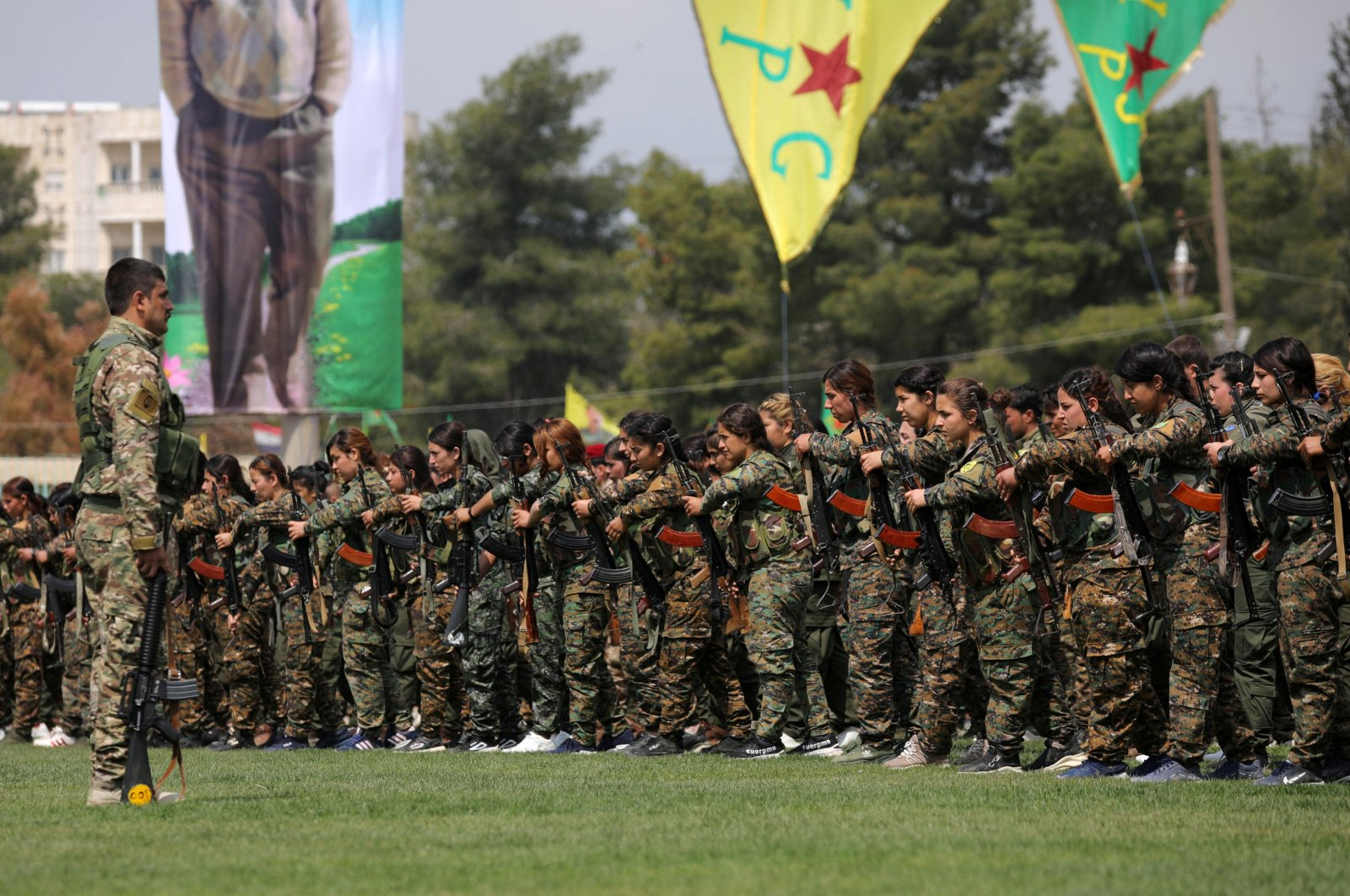 YPG terrorists stand near a banner depicting imprisoned PKK leader Abdullah Öcalan during a parade in Syria's Qamishli on March 28, 2019. (Reuters File Photo)