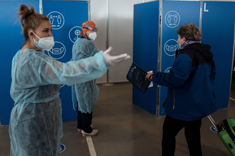 Il 1 ° maggio 2021, gli infermieri accolgono un passeggero per il test COVID-19 prima di imbarcarsi sulla nave da crociera Costa Smeralda a Savona, vicino a Genova, in Italia.  (Foto AFP)