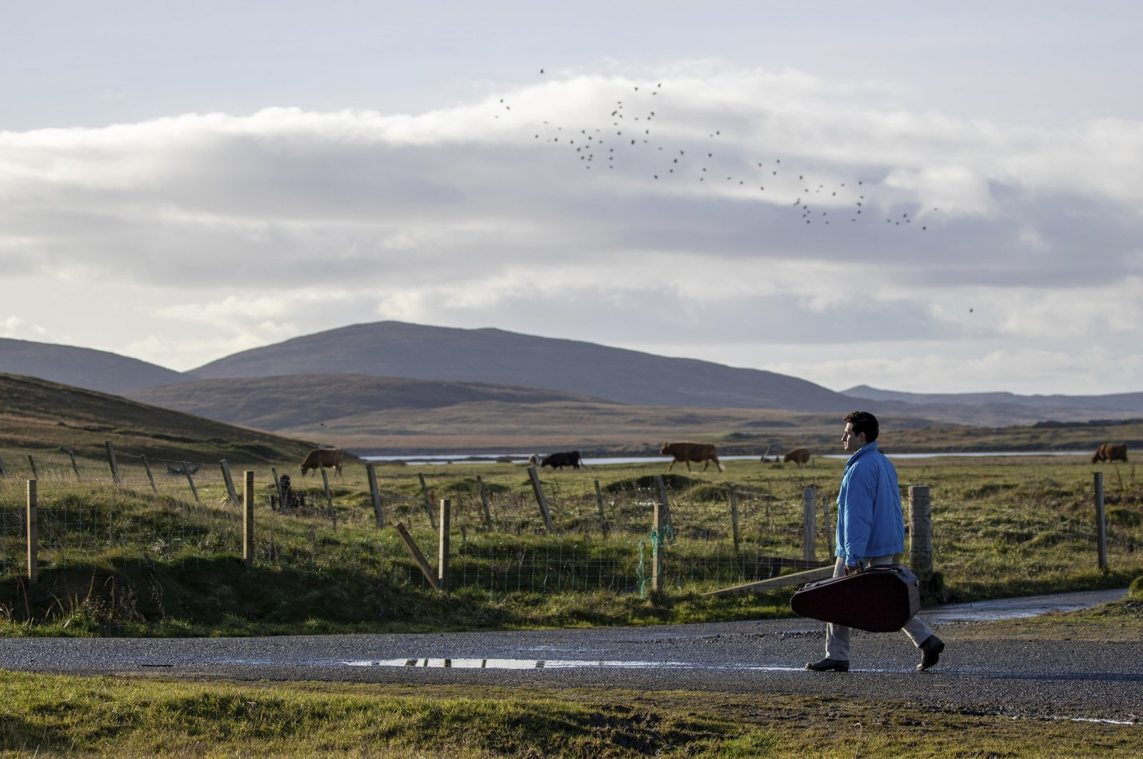 """In this image made from video provided by Focus Features, Amir El-Masry who stars as """"Omar"""" in the film """"Limbo"""" walks along a road on the Uist islands, in the Outer Hebrides, Scotland. (Focus Features via AP)"""