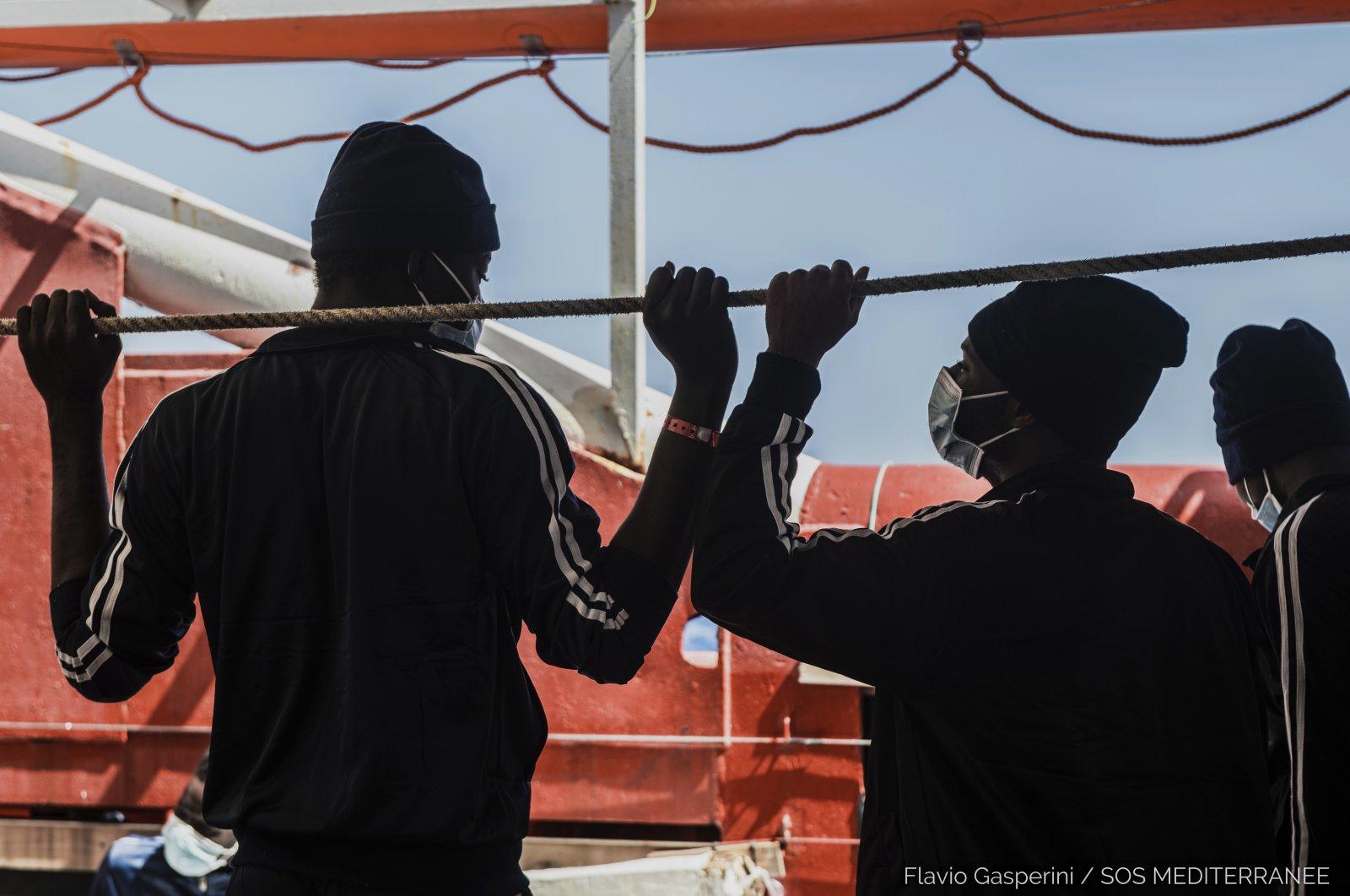 Migrants look at the sea from aboard the Ocean Viking during its navigation in the Mediterranean Sea, April 29, 2021. (SOS Mediterranee via AP)