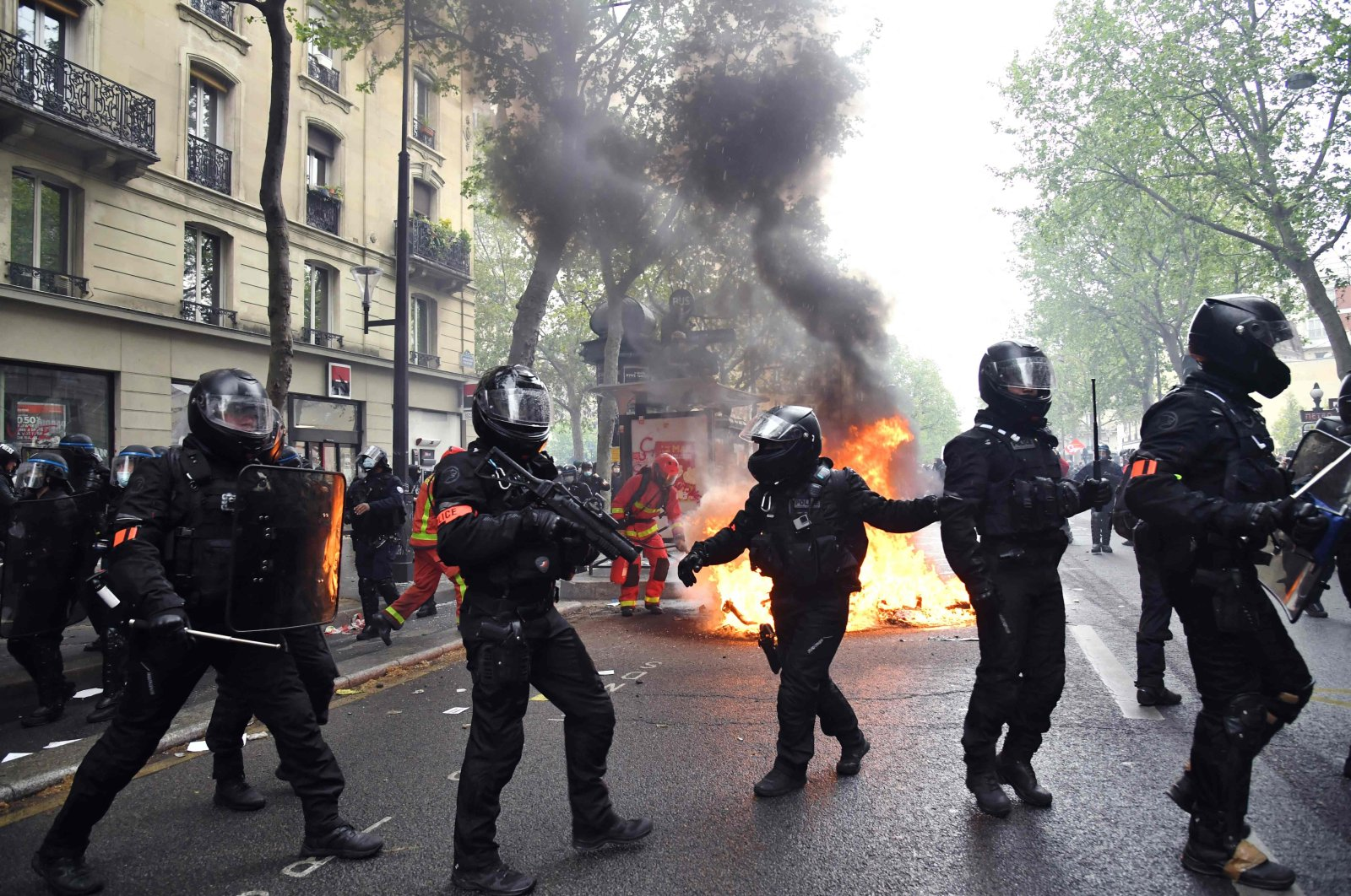 Police officers of the brigade of repression of violent action (BRAV) walk near a fire burning in the street during the annual May Day (Labor Day) rally in Paris, France, May 1, 2021. (AFP Photo)