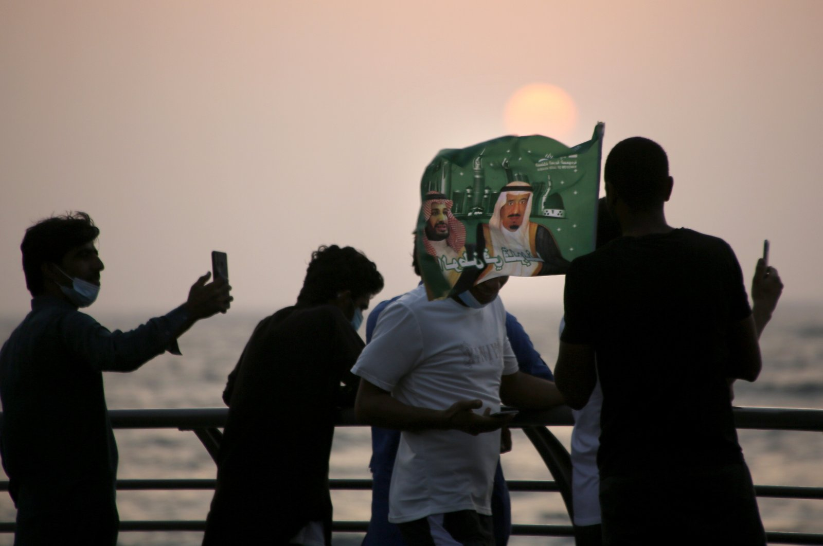 Saudis watch the sunset as they wave a flag with pictures of Saudi King Salman (R) and Crown Prince Mohammed bin Salman (L) during a celebration marking National Day to commemorate the unification of the country as the Kingdom of Saudi Arabia, in Jiddah, Saudi Arabia, Sept. 23, 2020. (AP Photo)
