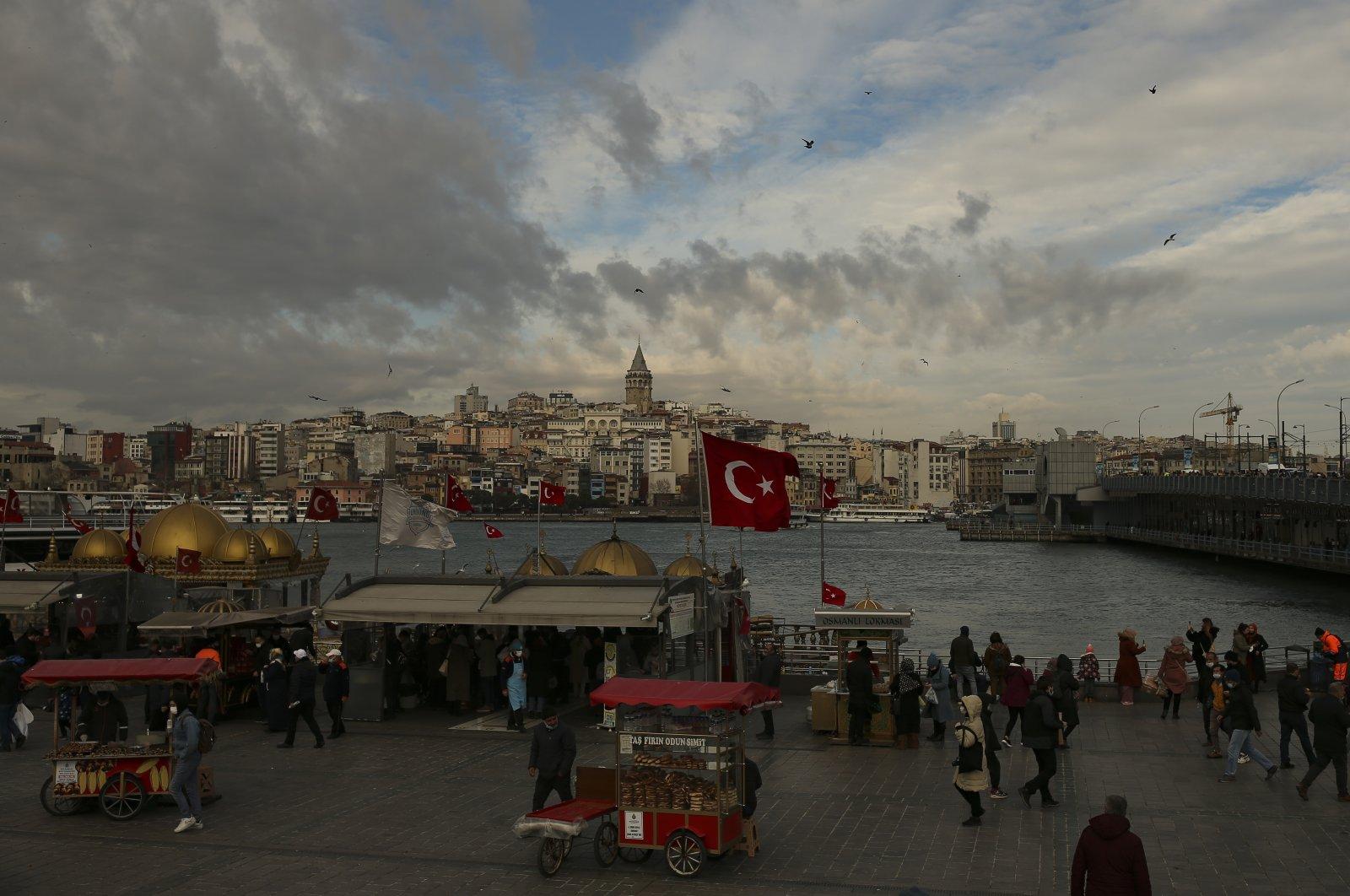 People wearing masks as protection against the coronavirus walk on Galata Bridge, Istanbul, Turkey, Jan. 29, 2021. (AP Photo)
