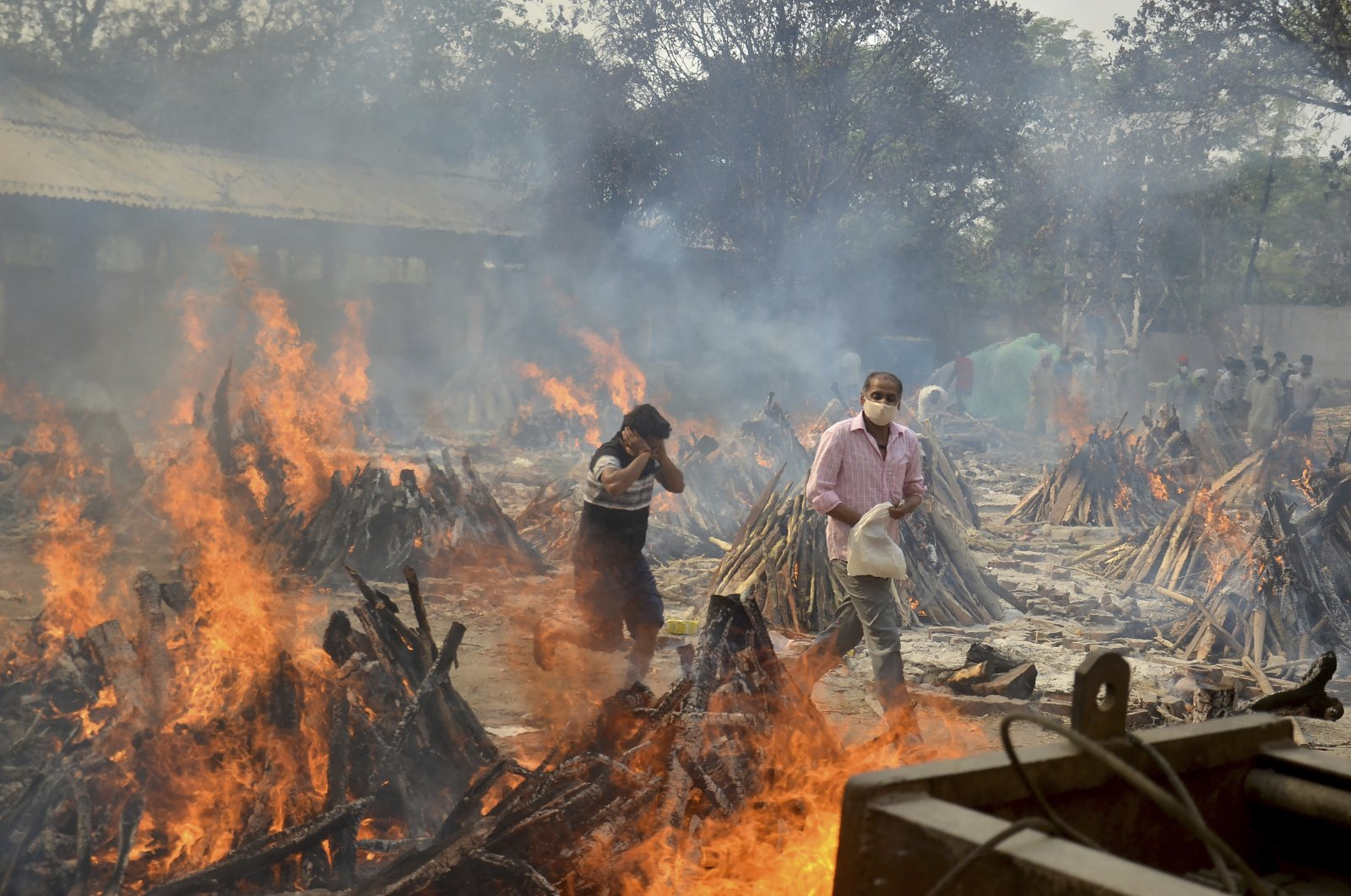 Relatives react to heat emitting from the multiple funeral pyres of COVID-19 victims at a crematorium in the outskirts of New Delhi, India, April 29, 2021. (AP Photo)