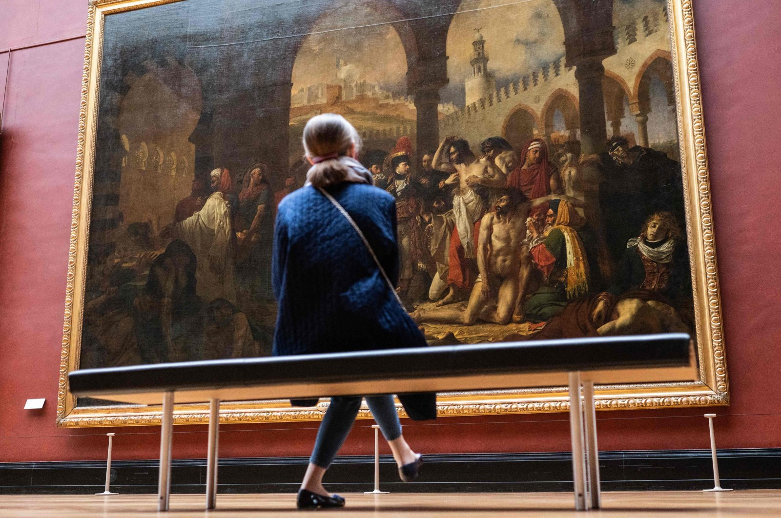 """A woman views the original 1804 painting of """"Bonaparte visiting the plague stricken in Jaffa"""" by French painter Antoine-Jean Gros, on display at the Louvre museum in Paris, France, April 29, 2021. (AFP Photo)"""