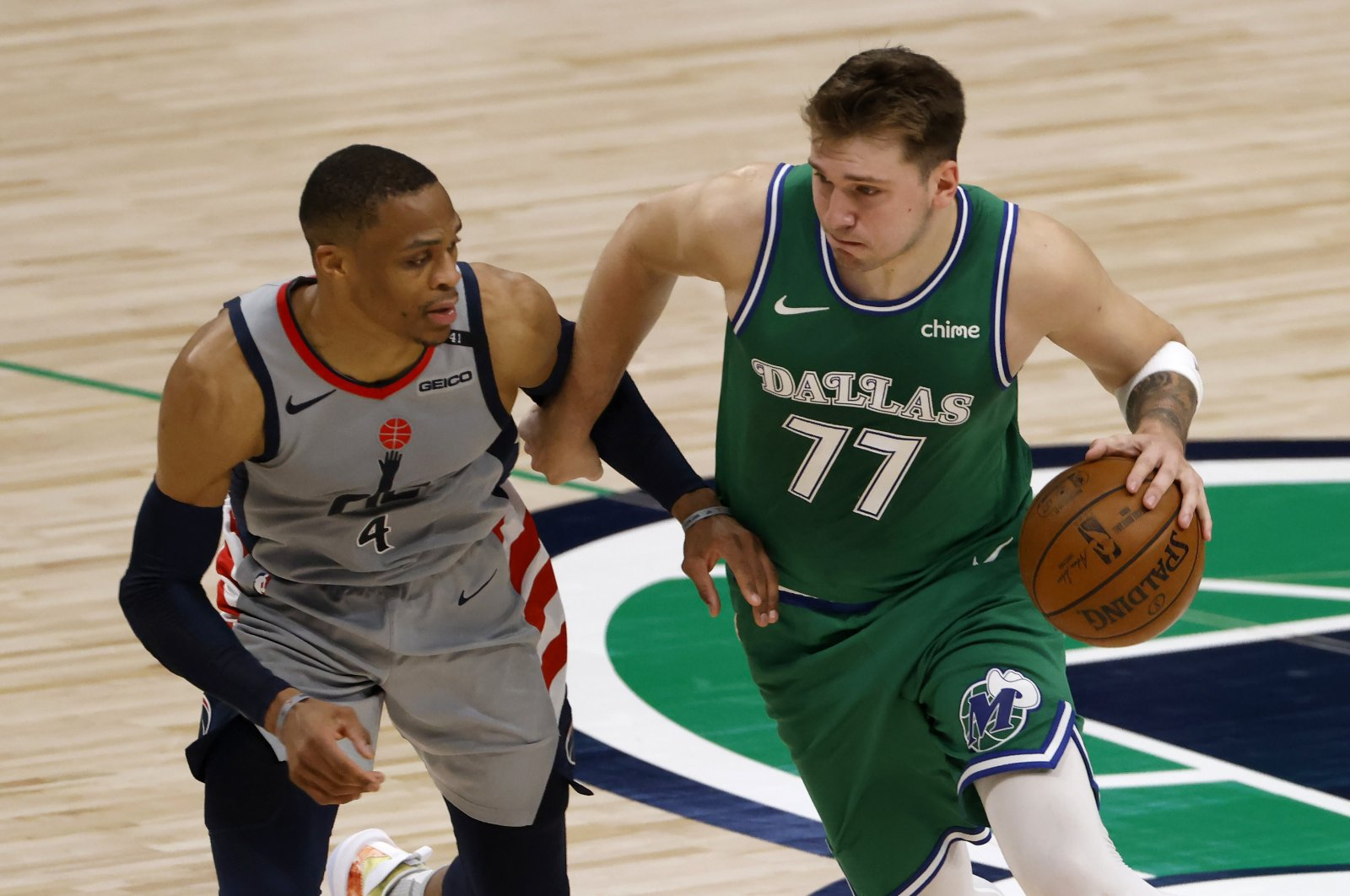 Dallas Mavericks guard Luka Doncic (R) handles the ball as Washington Wizards guard Russell Westbrook tries to slow him down during an NBA game, Dallas, U.S., May 1, 2021. (AP Photo)