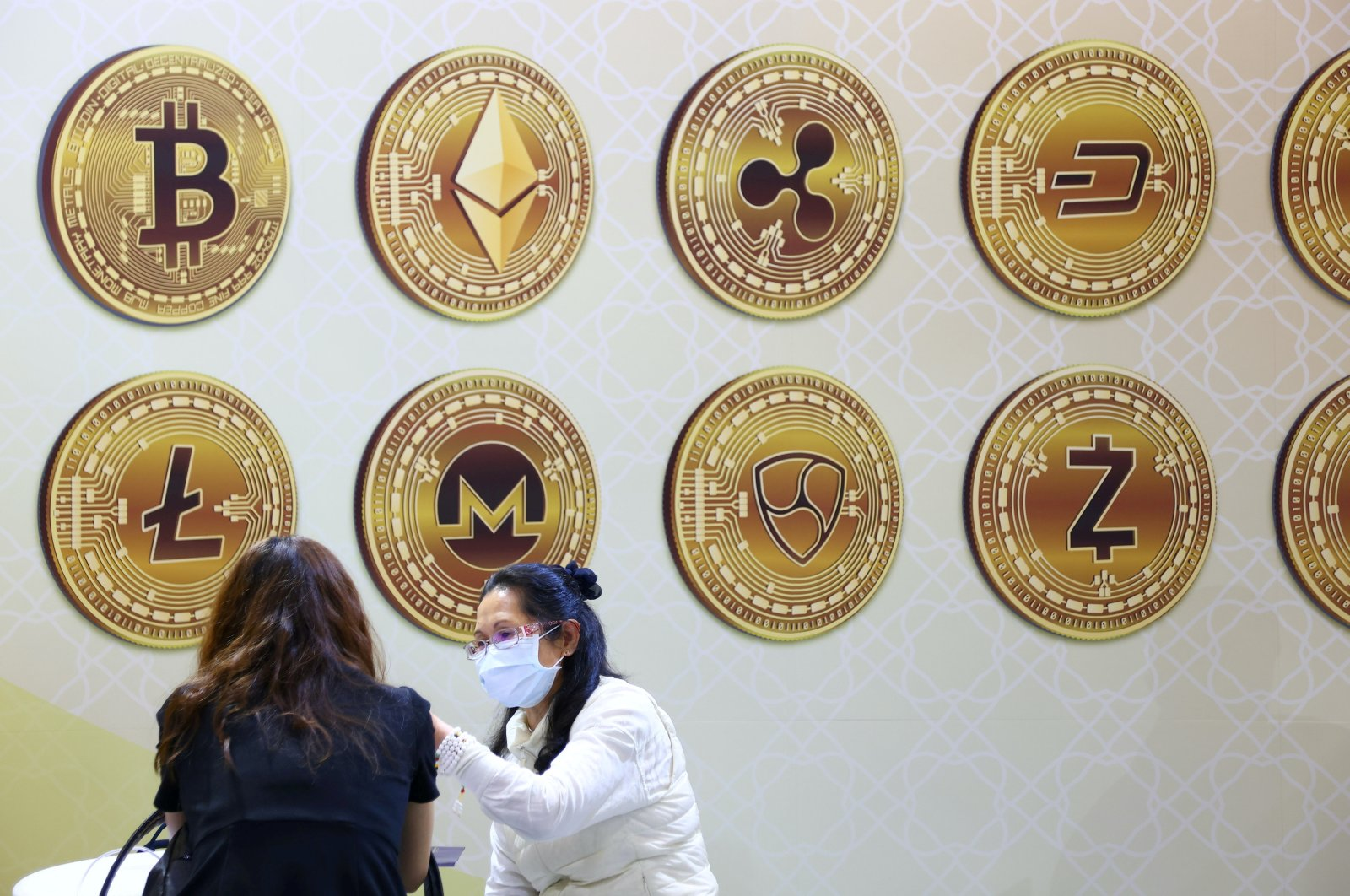 Customers talk against a backboard with cryptocurrency signs during the 2020 Taipei International Finance Expo in Taipei, Taiwan, Nov. 27, 2020. (Reuters Photo)