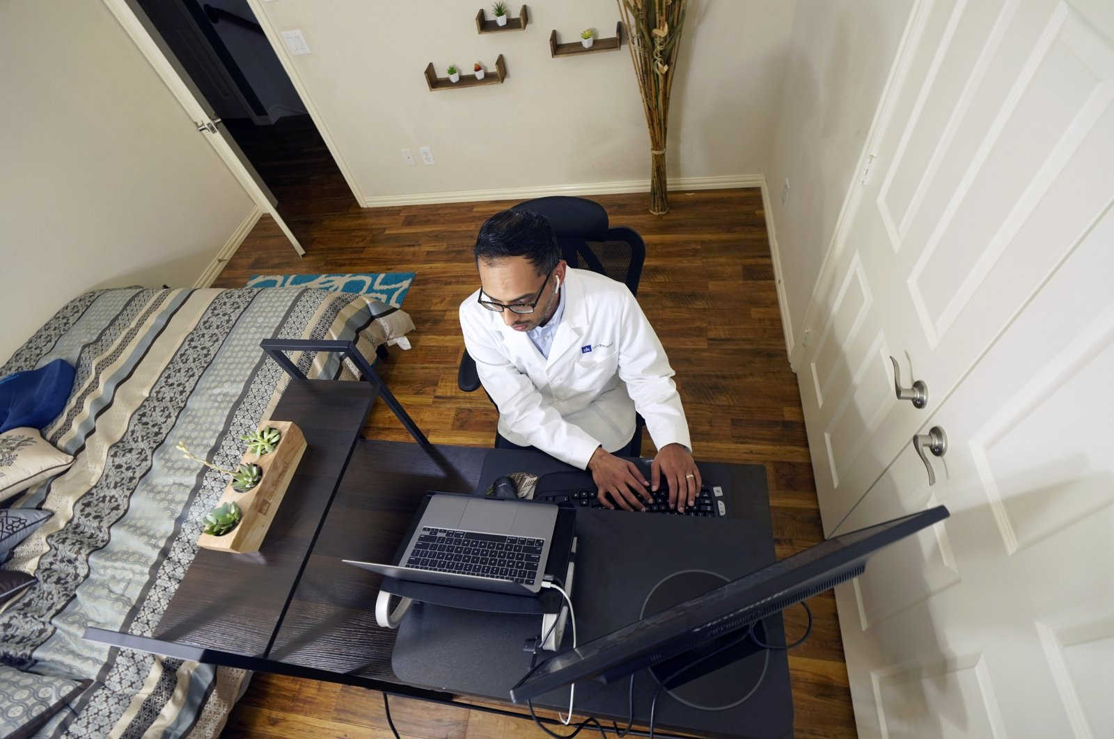 The medical director of Doctor on Demand, Dr. Vibin Roy, types notes as he listens to a patient during an online primary care visit from his home, Texas, the U.S., April 23, 2021. (AP Photo)