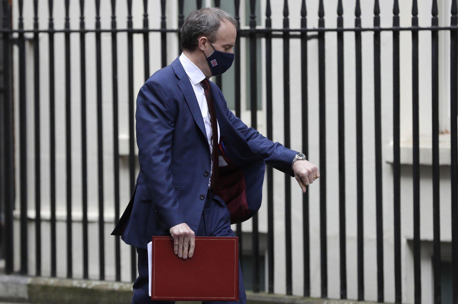 Britain's Foreign Secretary Dominic Raab checks his watch as he walks across Downing Street in London, Wednesday, Feb. 24, 2021. (AP Photo)