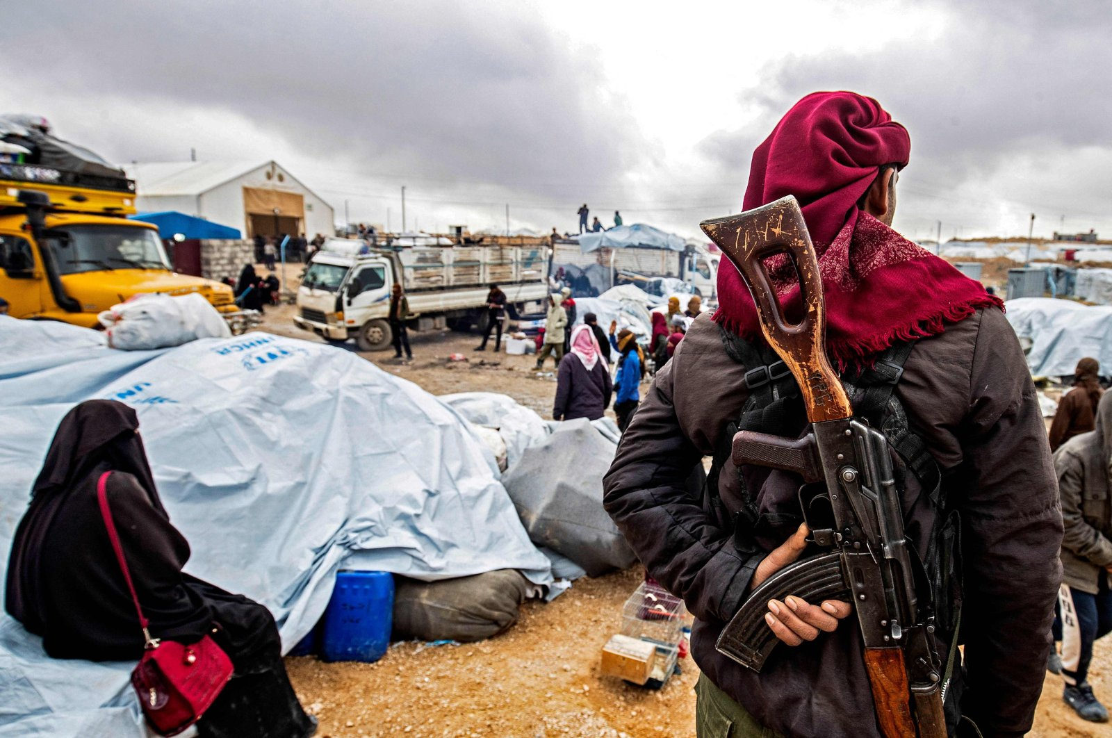 A YPG terrorist watches as families load their belongings onto trucks before leaving the YPG-run al-Hol camp holding relatives of Daesh terrorist group fighters, in the Hassakeh governorate in northeastern Syria, Nov. 16, 2020. (Photo by Delil Souleiman/AFP)