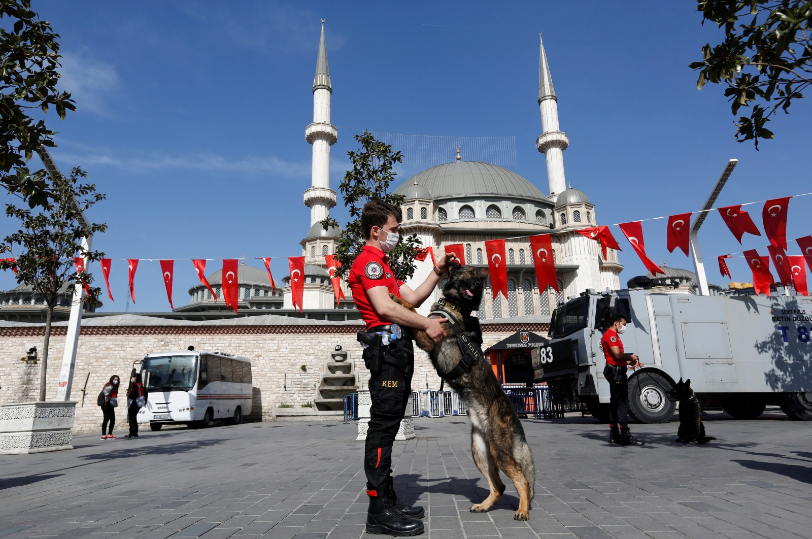 "A member of the Turkish Police Dog Training Center plays with a K-9 dog at Taksim Square during a nationwide ""full closure"" imposed to slow the rate of the coronavirus contagion, in central Istanbul, Turkey May 1, 2021. (Reuters Photo)"