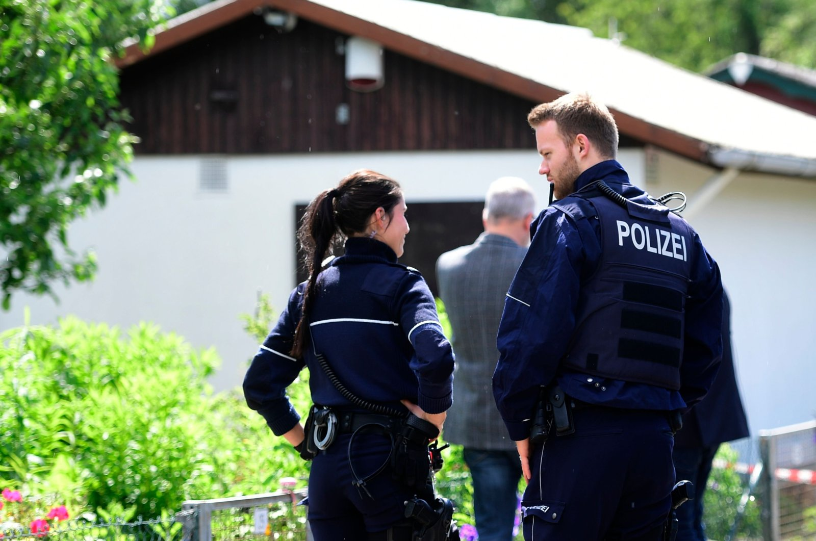 Police officers stand in front of a summer house where the sexual abuse of children is suspected to have taken place in Muenster, western Germany on June 6, 2020. (AFP Photo)