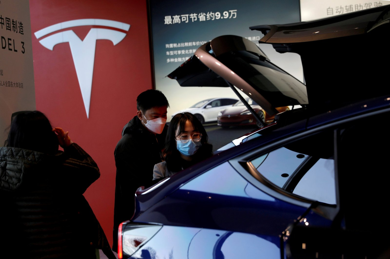 Visitors wearing face masks check a China-made Tesla Model Y sport utility vehicle (SUV) at the electric vehicle maker's showroom in Beijing, China, Jan. 5, 2021. (Reuters Photo)