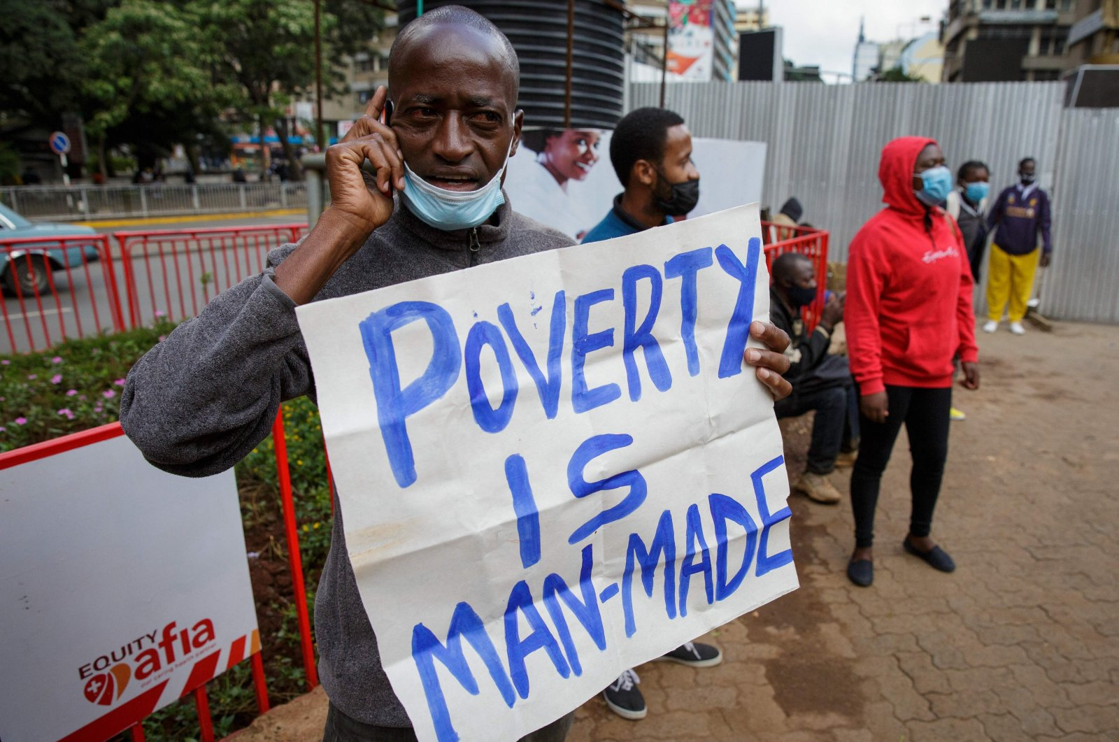 "A protester holds a message ""Poverty is man-made"" as they demand the Kenyan government take action for better living conditions in the COVID-19 pandemic during a May Day rally marking the international labor day in Nairobi, Kenya, May 1, 2021. (AFP Photo)"