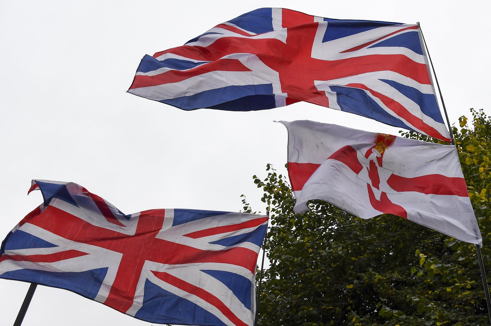 Northern Ireland and Union flags flutter outside the Houses of Parliament, in London, Oct. 14, 2019. (AP Photo)