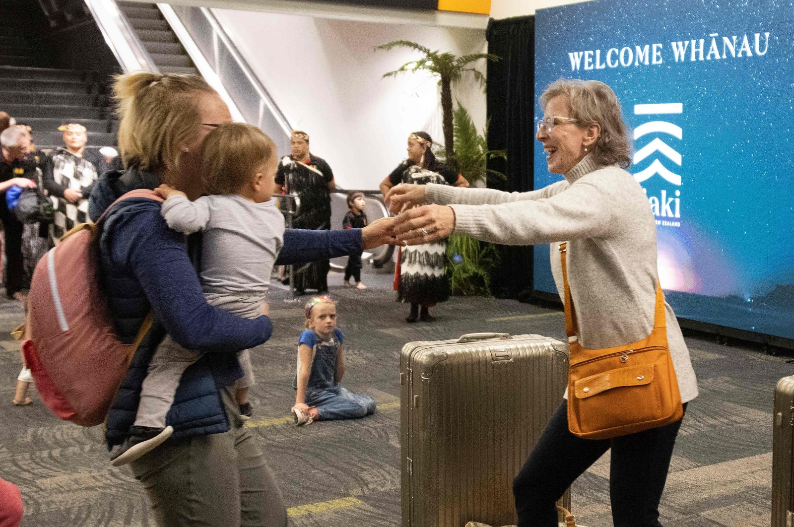 """Families are reunited as travelers arrive on the first flight from Sydney, as Australia and New Zealand opened a trans-Tasman quarantine-free """"travel bubble,"""" Wellington, New Zealand, April 19, 2021. (AFP Photo)"""