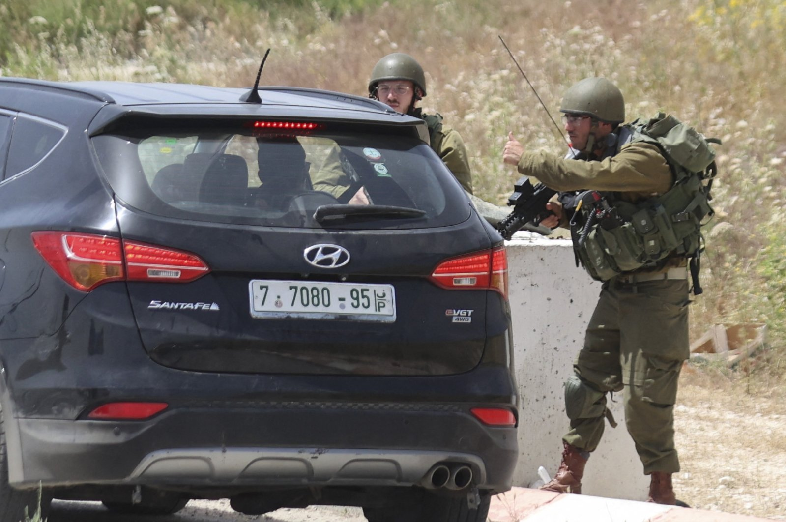 Israeli soldiers search cars at the Hawara checkpoint, the southern entrance to Nablus city in the illegally occupied West Bank, on May 3, 2021 (AFP Photo)