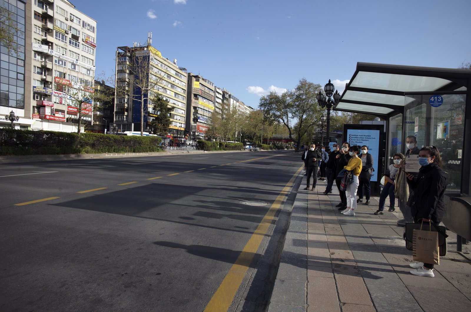 People wait for a bus on a deserted main road in Ankara, Turkey, April 30, 2021. (AP Photo)