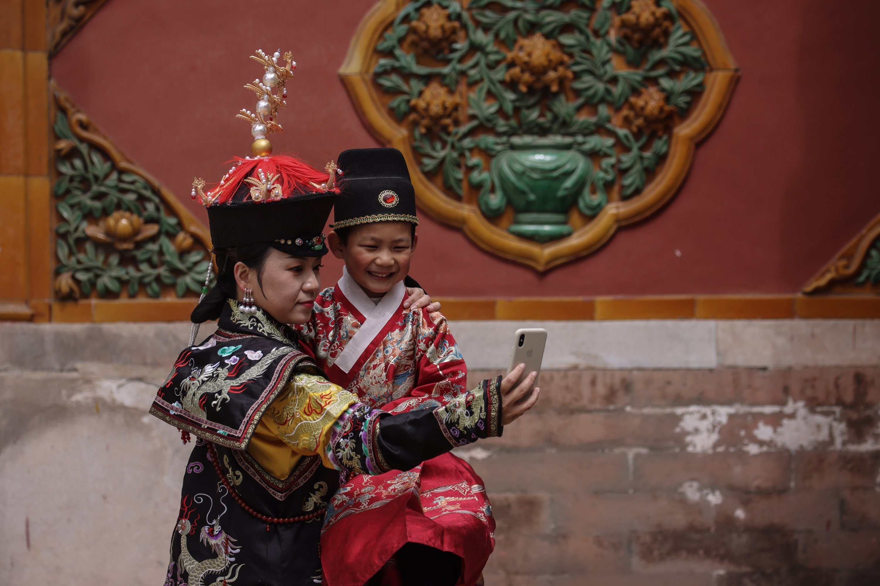 Tourists wearing Chinese traditional clothes take selfies in the Forbidden City during a media event while visiting the Forbidden City in Beijing, China, April 16, 2021. (EPA Photo)