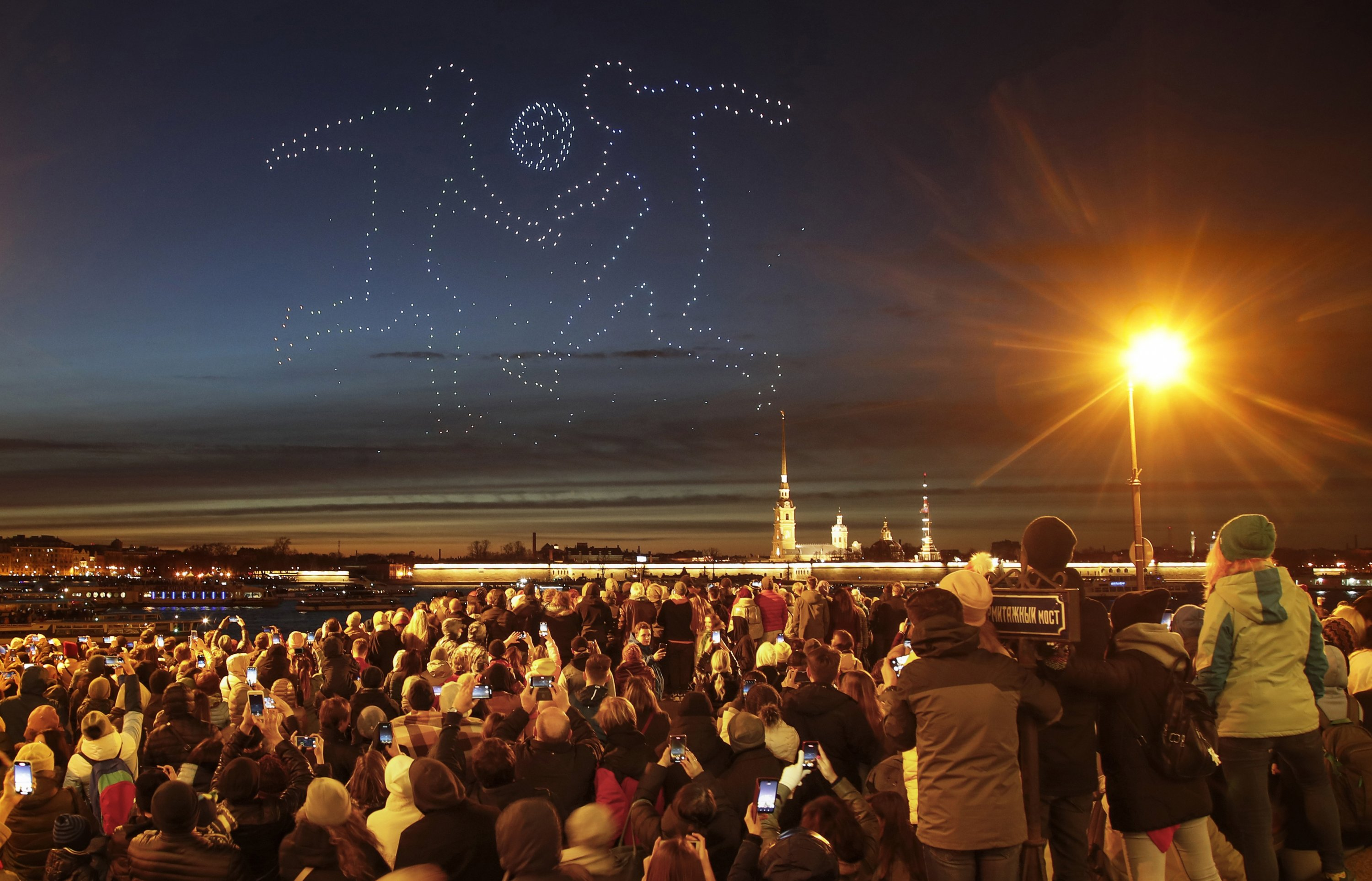 People watch glowing drones depicting soccer players during a drone show over the Saints Peter and Paul Cathedral in St. Petersburg, Russia, May 2, 2021. St. Petersburg will host seven postponed UEFA EURO 2020 matches, including a quarterfinal. (AP Photo)